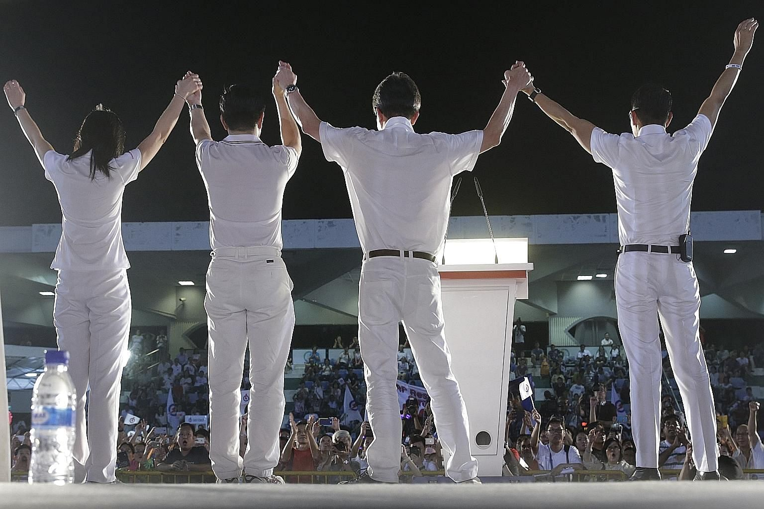 PAP East Coast GRC candidates (from left) Jessica Tan, Lee Yi Shyan, Lim Swee Say and Maliki Osman acknowledging the crowd after an election rally held at Bedok Stadium yesterday.