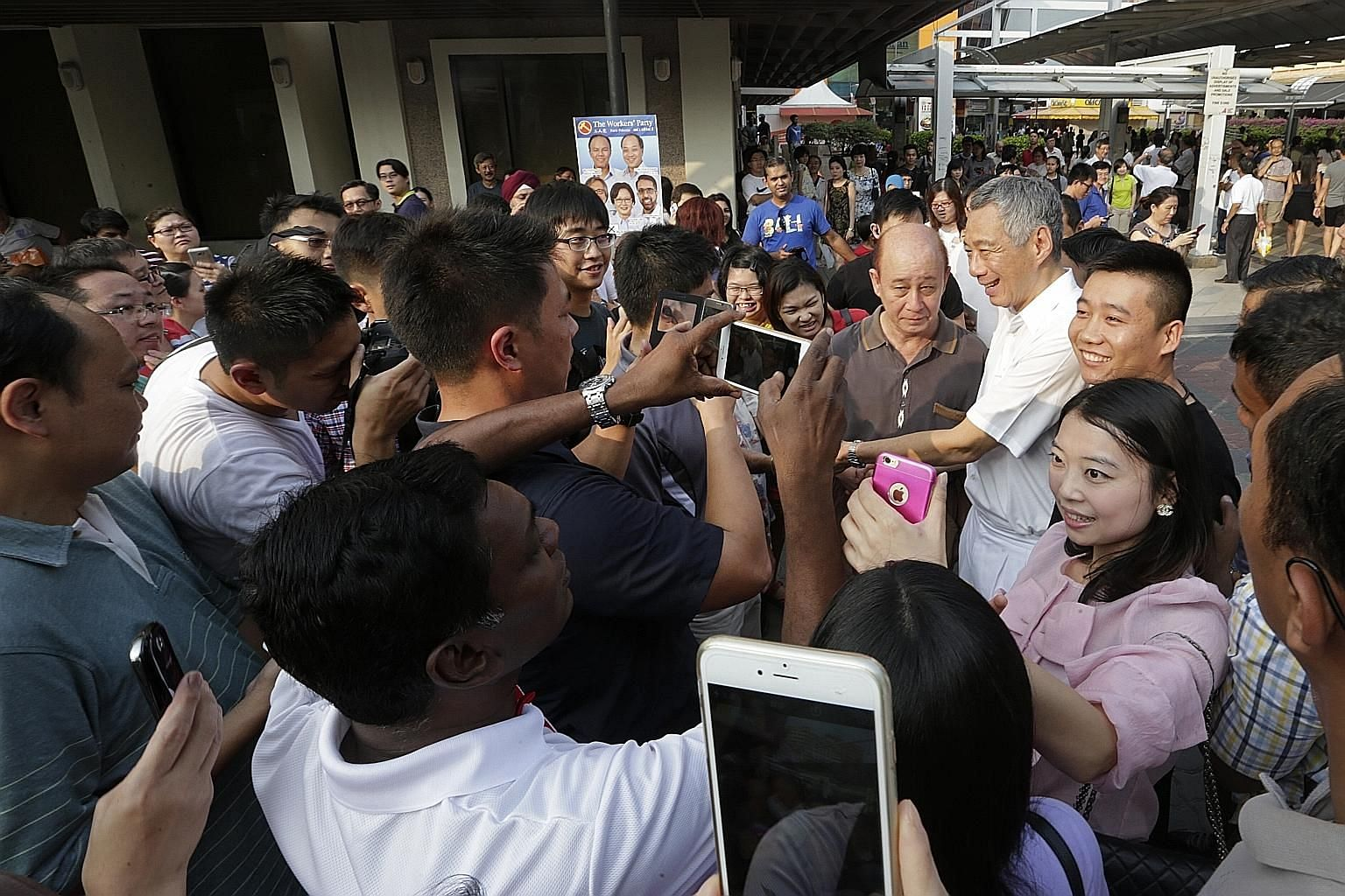 Prime Minister Lee Hsien Loong surrounded by people wanting to have photographs taken with him outside Hougang MRT station during a walkabout with the PAP candidates for Aljunied GRC yesterday.