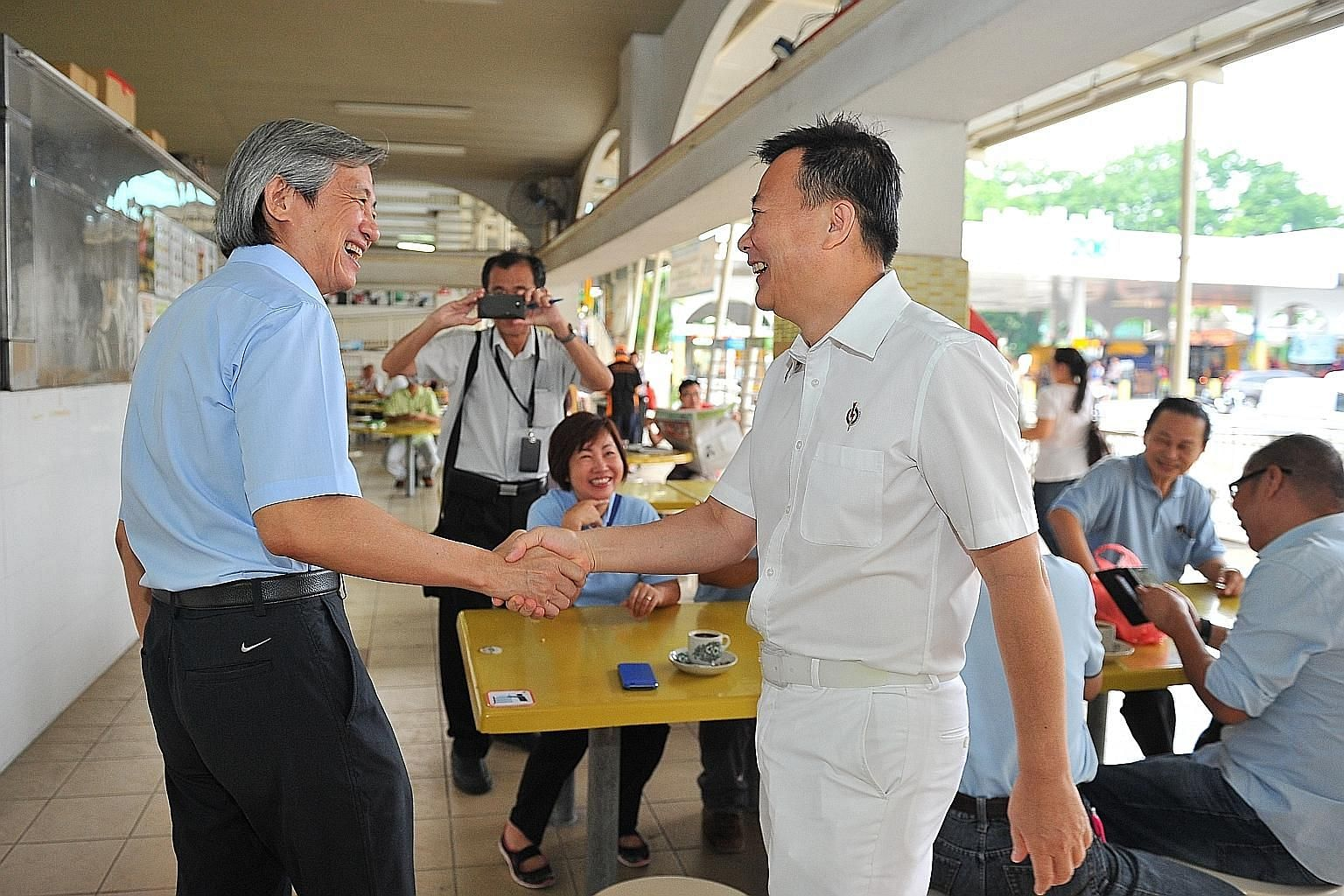 WP candidate Chen Show Mao (left) and PAP candidate Victor Lye greeting each other at Kovan Hougang Market and Food Centre yesterday. The next two days will be a battle to win over swing voters, with the daily schedules of both parties packed with wa