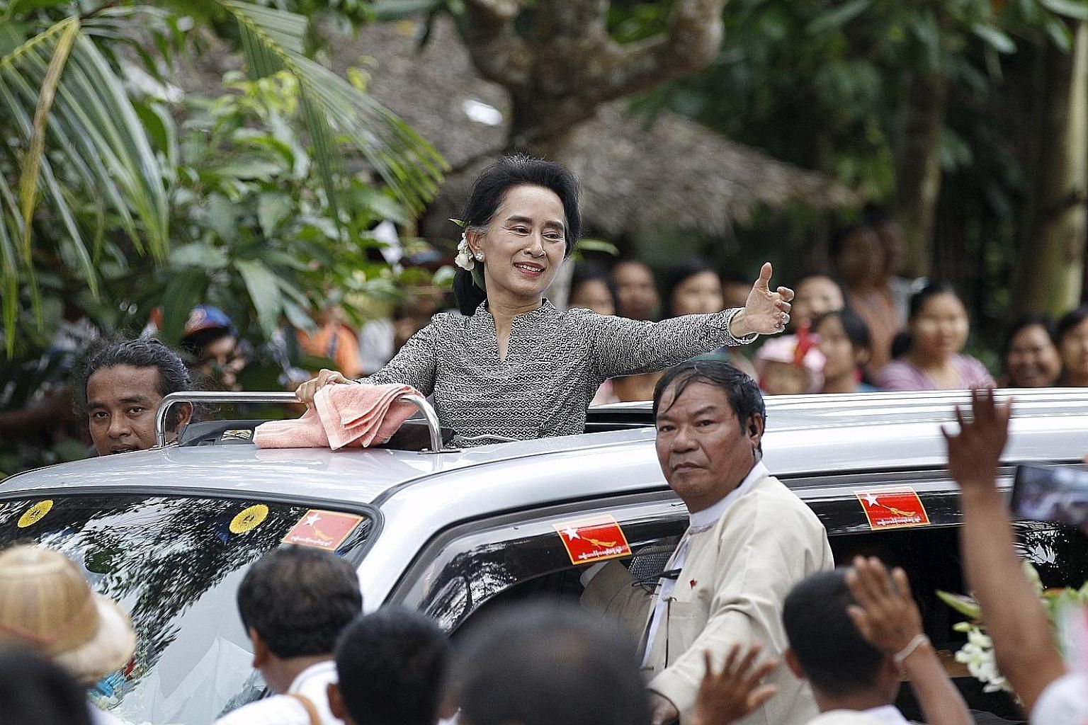Myanmar pro-democracy leader Aung San Suu Kyi waving to supporters while on the third week of her campaign in Kawhmu, outside Yangon, yesterday. Myanmar's powerful army chief has said women are welcome to lead the country, but hurdles still stand in