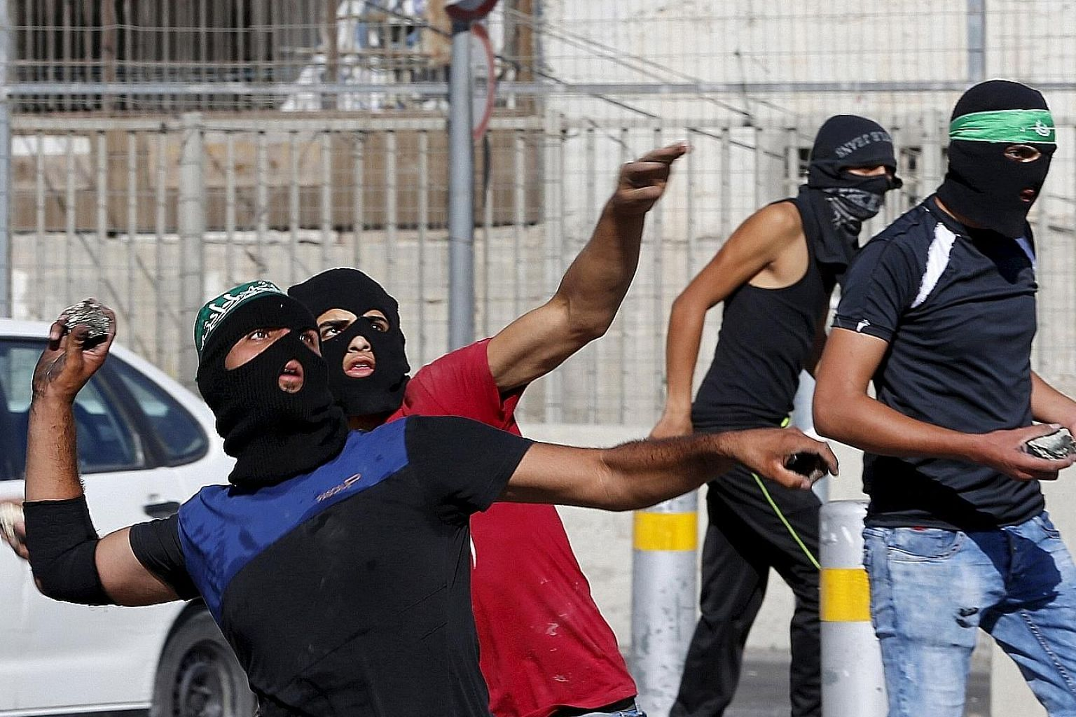 Palestinians hurling stones at police last week at a checkpoint between the Shuafat refugee camp and Jerusalem. The government is preparing legislation for minimum prison terms for adults who throw rocks and firebombs.