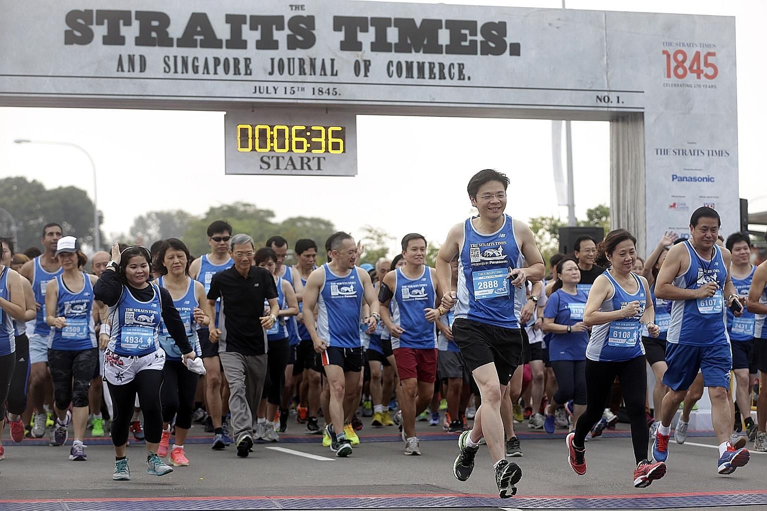 Minister for Culture, Community and Youth Lawrence Wong (foreground, third from right), the guest of honour at the event, participating in the 5km fun run with Singapore Press Holdings (SPH) chairman Lee Boon Yang (in black), Straits Times managing e