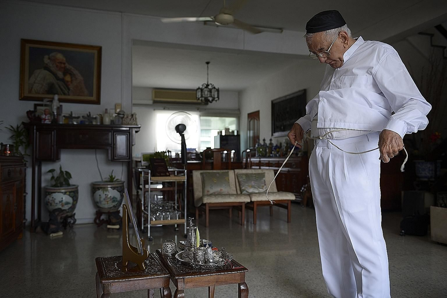 Mr Rustom Ghadiali, president of the Parsi Zoroastrian Association and one of the five priests here, praying at home.