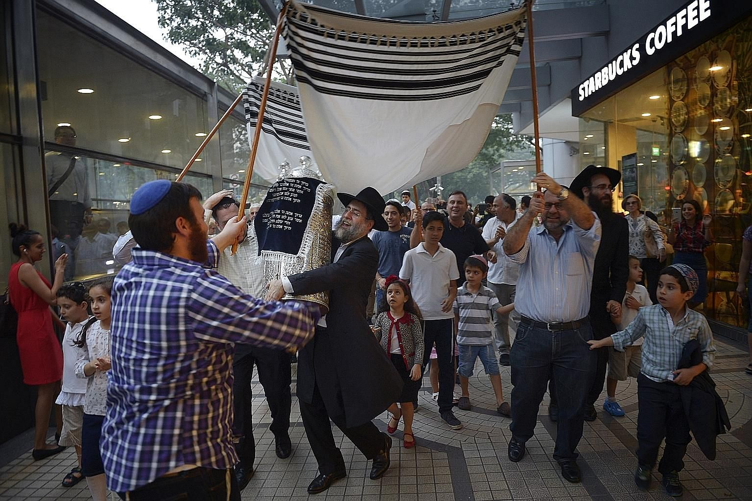 Rabbi Abergel holds a newly completed set of Torah as he and other members of the Jewish community celebrate on the streets outside the Maghain Aboth Synagogue. The joyous event usually concludes with a festive meal.