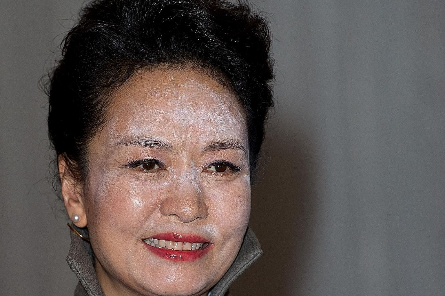 """Above: Photos of Ms Peng Liyuan at a reception hosted by the Lord Mayor of London show a heavy dusting of white powder on her forehead and nose. Left: Ms Peng, wearing a """"dignified and graceful"""" blue silk coat dress, arriving with Queen Elizabeth at"""