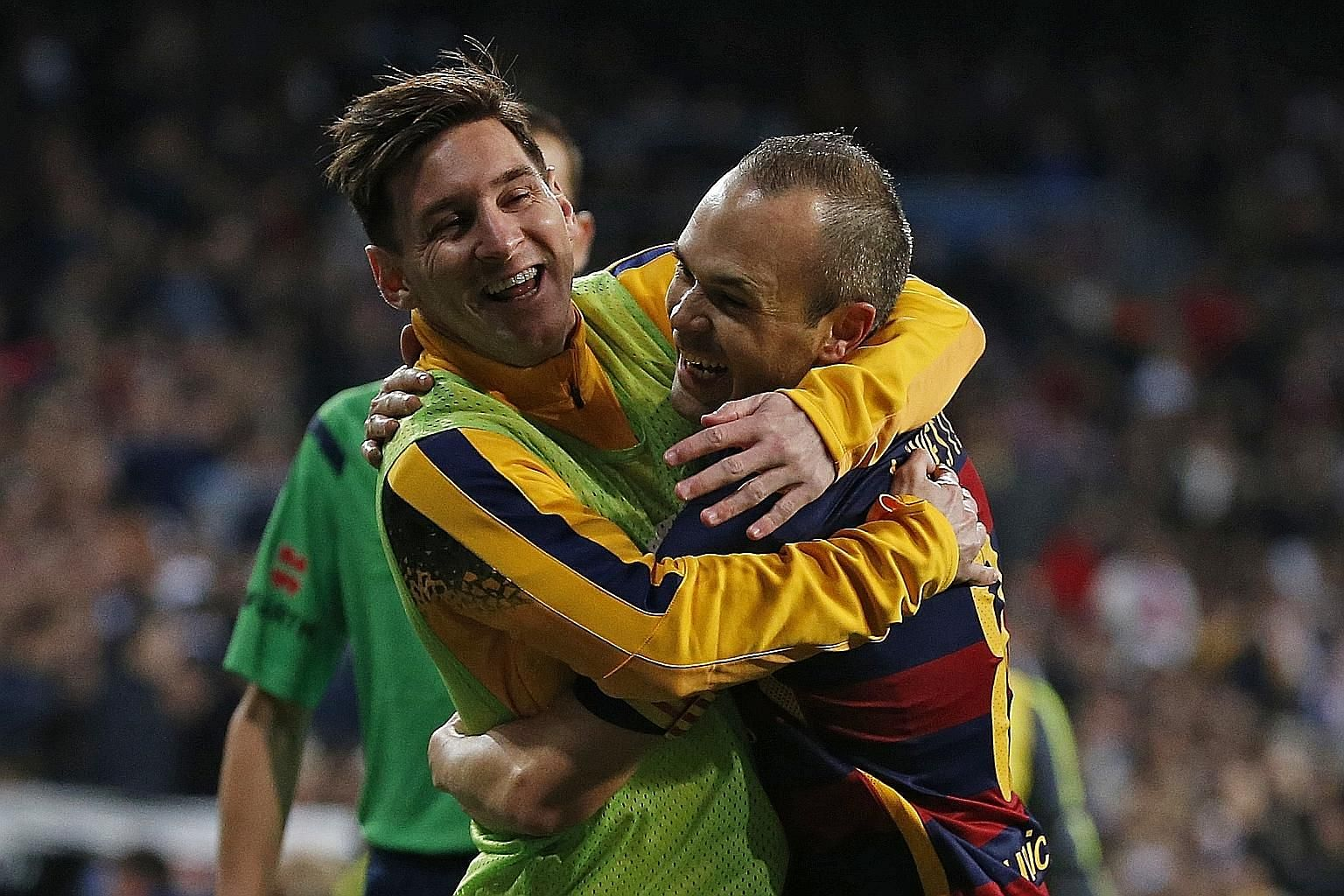 Lionel Messi (left) embracing Andres Iniesta after the latter had scored the third goal for Barcelona against Real Madrid on Saturday. Messi, who started on the bench, set up the last goal of the emphatic 4-0 victory.