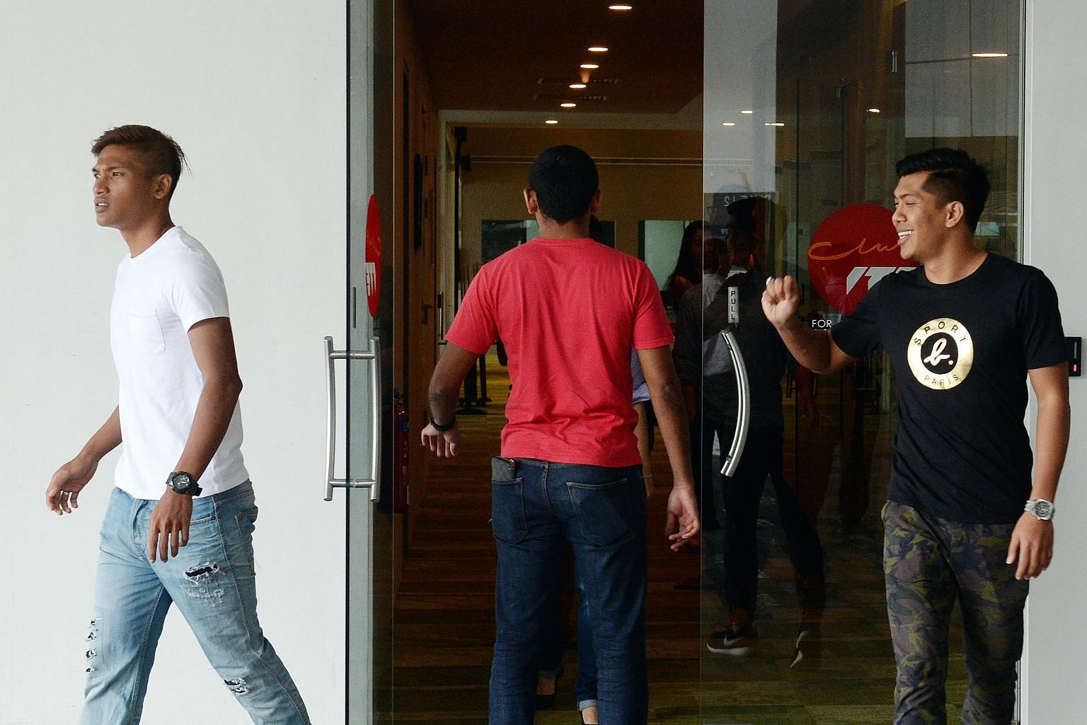 LionsXII half-brothers Khairul Nizam (left) and Khairul Amri leaving yesterday's meeting. The FAS has assured the bulk of LionsXII players that they will be guaranteed contracts on the same salaries next year.