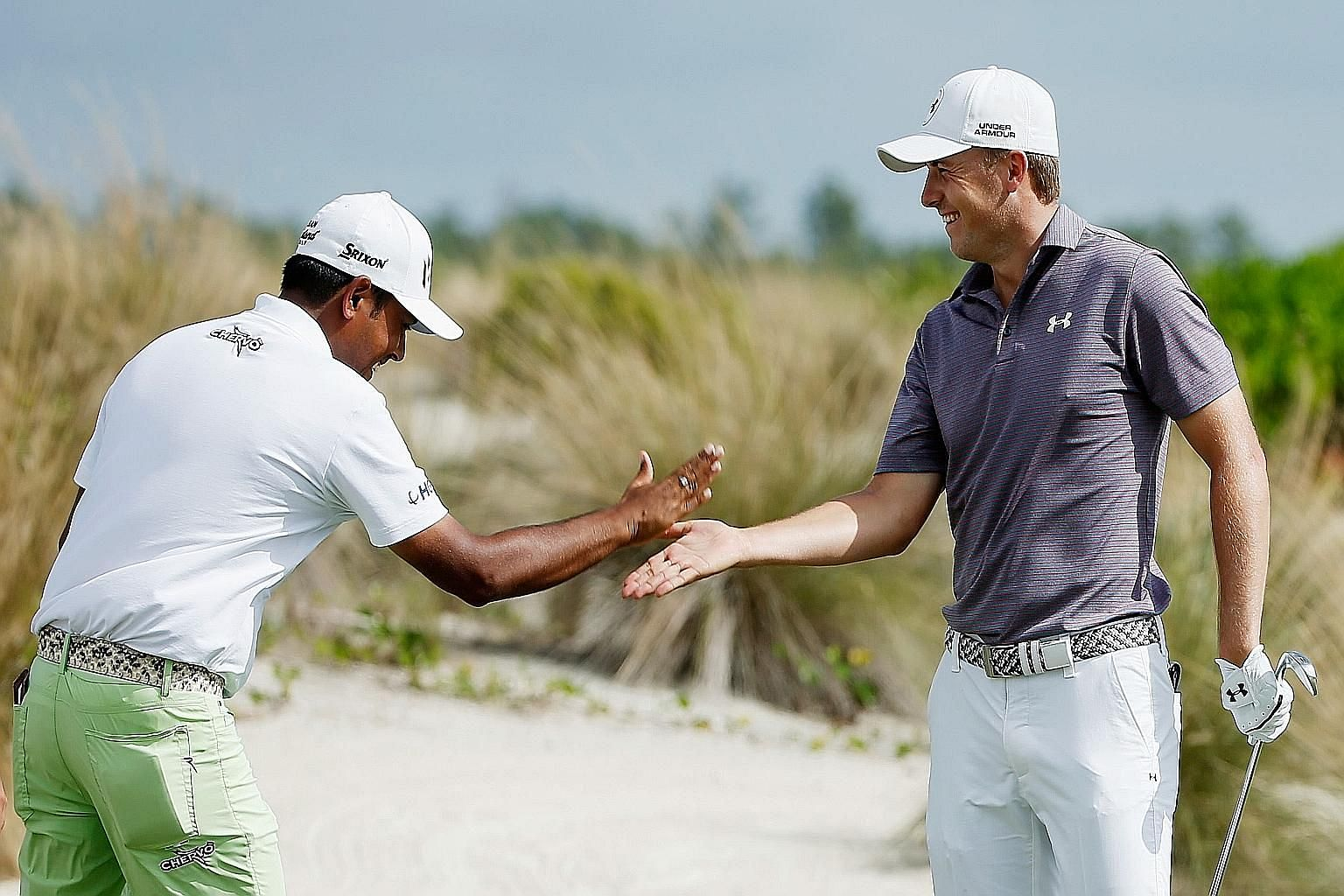 India's Anirban Lahiri (left) shares Jordan Spieth's joy after the defending champion aced the second hole.