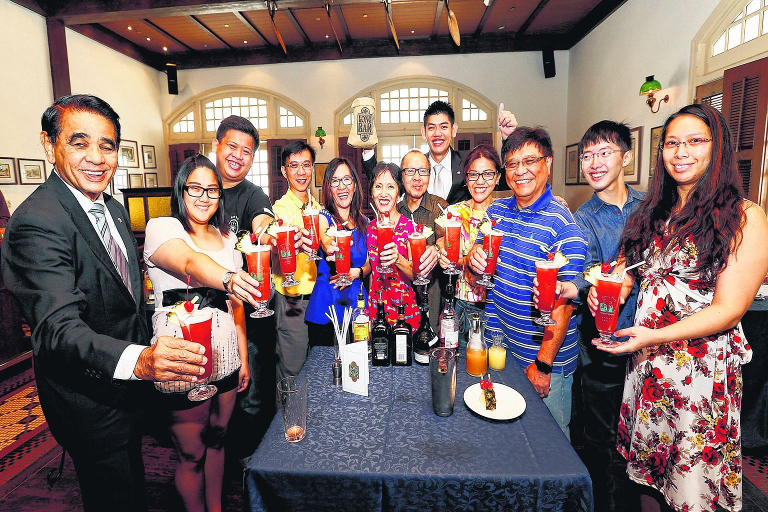 Raising a toast with their Singapore Slings in the Raffles Hotel Long Bar are (from left) Raffles Hotel resident historian Leslie Danker, 76; Ms Eunicia Tan, 22; Mr Gibson Chua, 25; Mr Gary Tan, 51; Ms Elin Loo, 49; Ms Irene Tan, 58; Mr Patrick Tan,