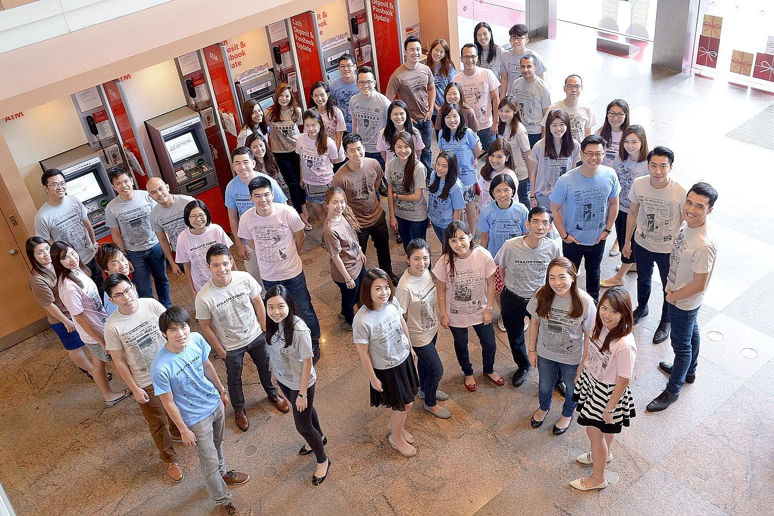 Fifty OCBC Bank employees (left) donned T-shirts produced by The Straits Times on Friday to commemorate the newspaper's 170th anniversary. The bank bought 200 T-shirts, which feature historical front pages of The Straits Times, for its staff voluntee