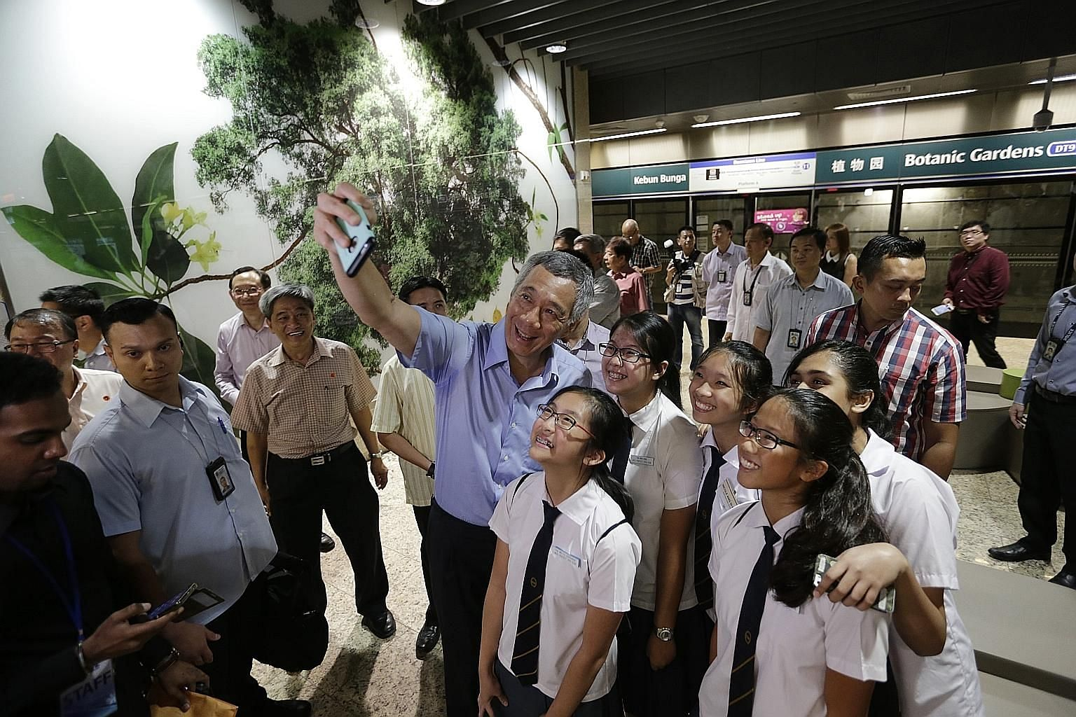 Prime Minister Lee Hsien Loong taking a wefie with students from Methodist Girls' School yesterday during the Downtown Line 2's opening ceremony at Botanic Gardens Station.