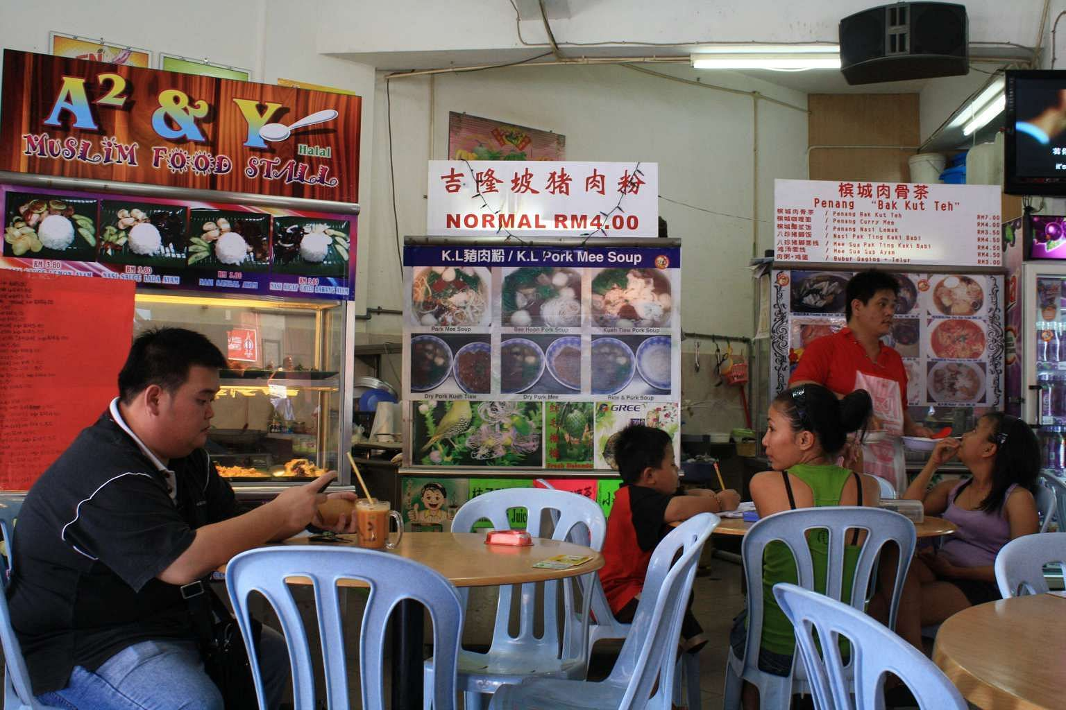 A coffee shop in Sibu, Sarawak, where a Muslim food stall stands beside a pork mee soup stall and another selling bak kut teh (pork rib soup).