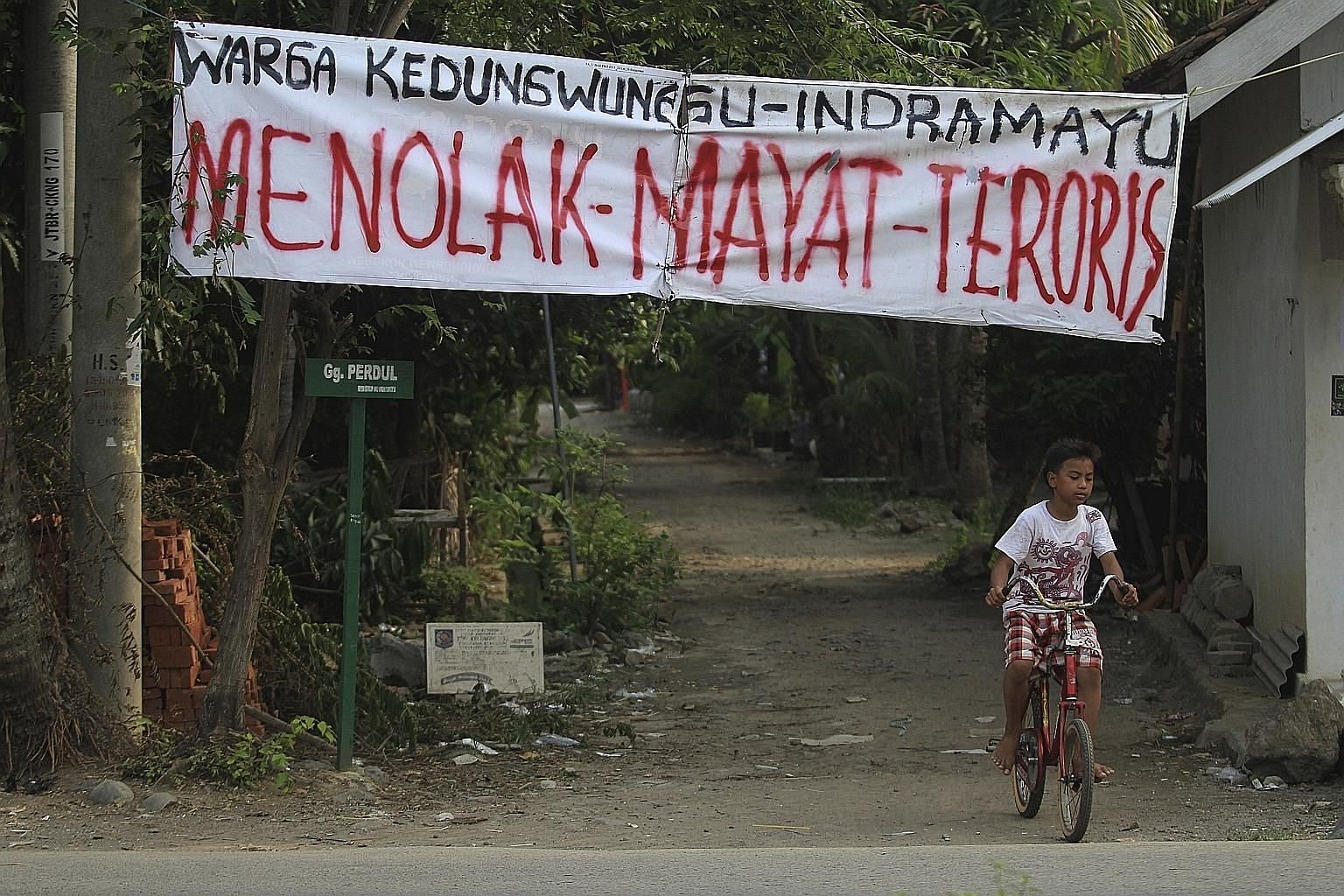 "A banner that reads ""Reject Terrorist's Body"" hanging over the entrance to Kedungwungu, home village of Ahmad Muhazin, one of the militants involved in last Thursday's terror attack in Jakarta."