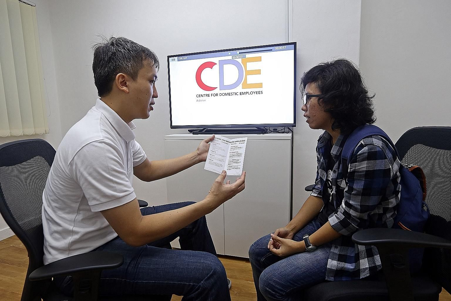 CDE senior manager Michael Tan speaking to domestic worker Ucik Indrawati at NTUC's new Centre for Domestic Employees at Goldhill Centre yesterday. The centre has five staff members, who speak English and Bahasa Indonesia, and is recruiting staff wit