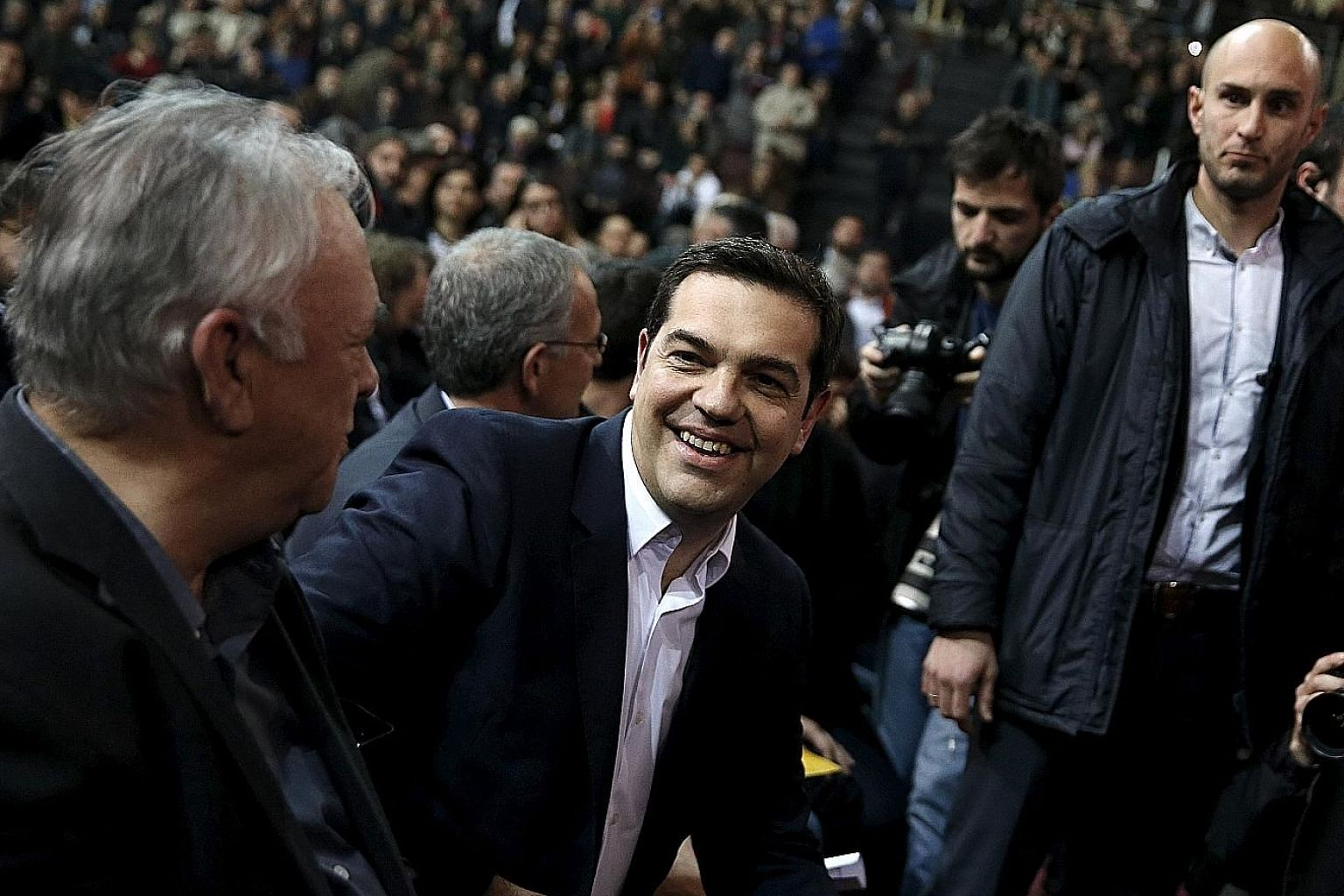 Greek Prime Minister Alexis Tsipras (centre) in a relaxed mood before making a speech to mark his first year in office in Athens. He is headed towards a showdown over Greece's social security reforms, which he wants to push through by raising contrib