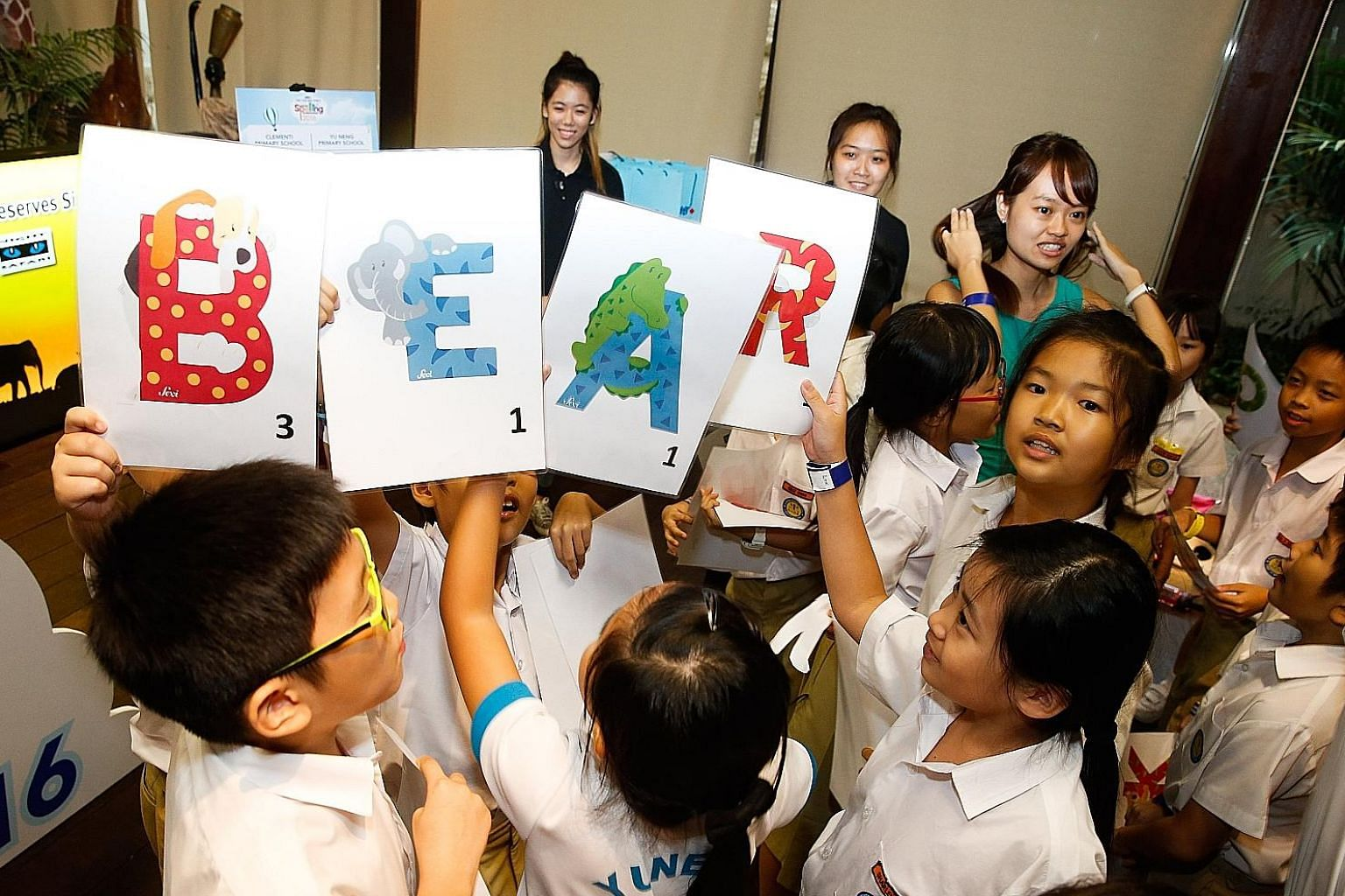 """Yu Neng Primary School pupils demonstrating their knowledge of animal names at the Singapore Zoo yesterday, at the launch of the fifth RHB-The Straits Times National Spelling Championship. The most difficult word they spelled, """"rhinoceroses"""", was als"""