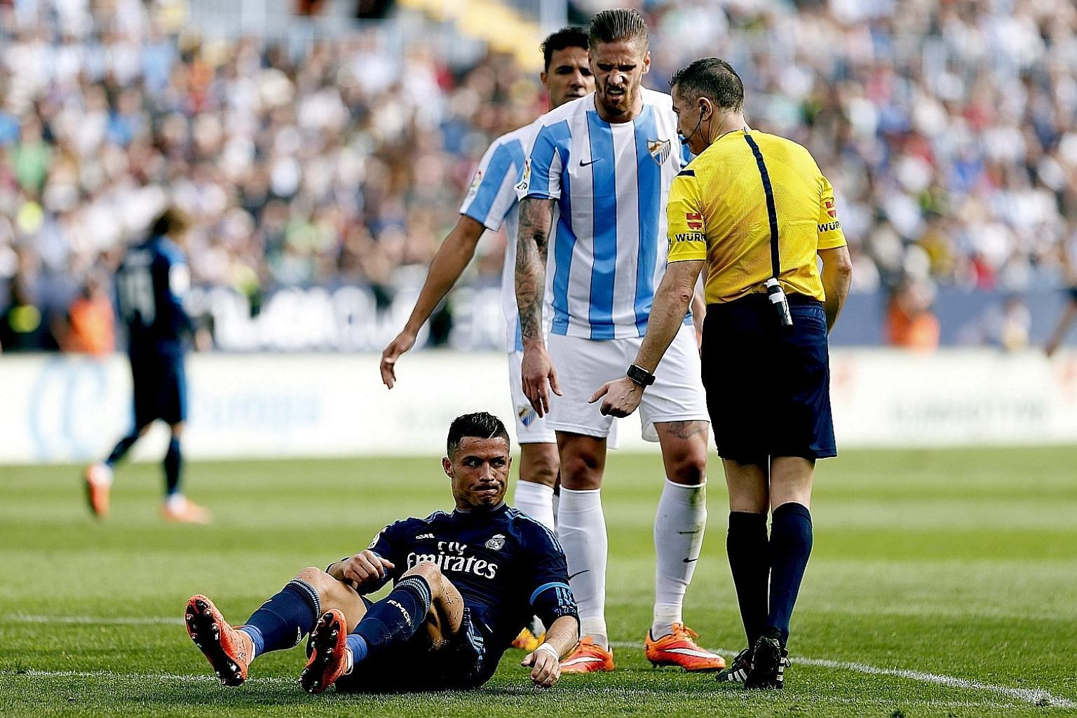 Cristiano Ronaldo after being knocked down by Malaga's Raul Albentosa (centre) during the 1-1 La Liga draw on Sunday.