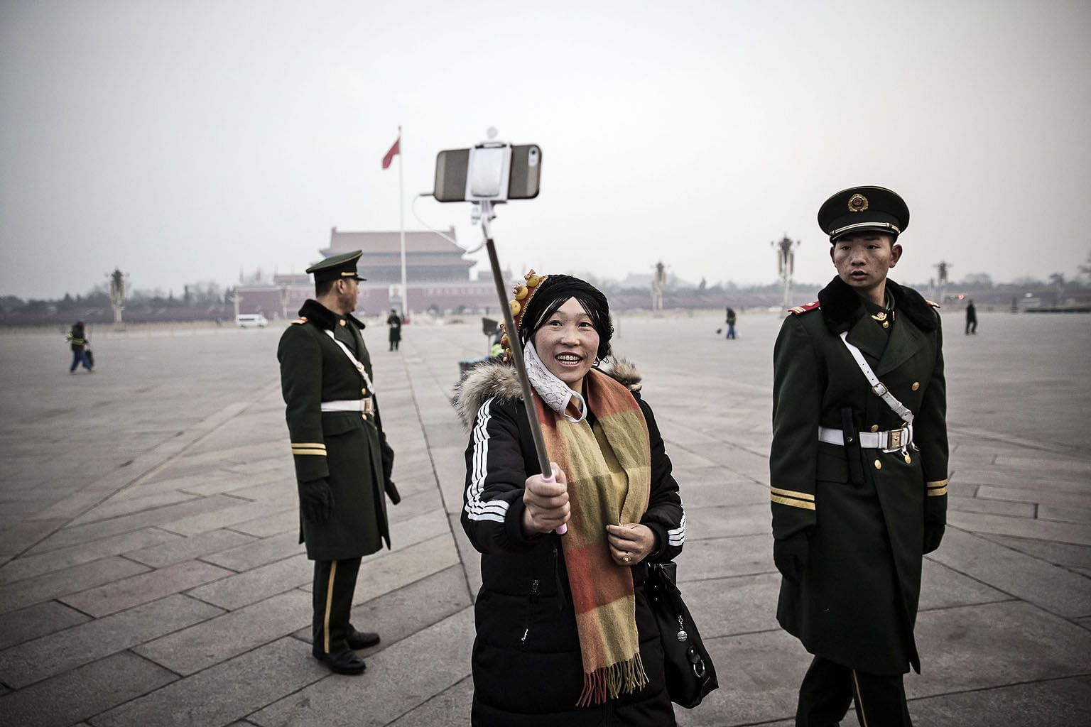 A visitor to Tiananmen Square on Thursday using a smartphone on a selfie stick to capture a shot with a paramilitary police officer after the daily flag-raising ceremony there.