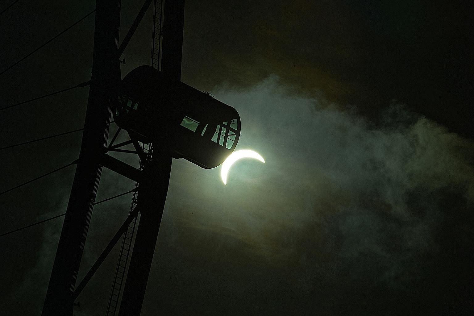 The Sun seen as a crescent at 8.29am yesterday, with a capsule of the Singapore Flyer in the foreground. In Singapore, the solar eclipse started at about 7.20am and peaked just past 8.20am.
