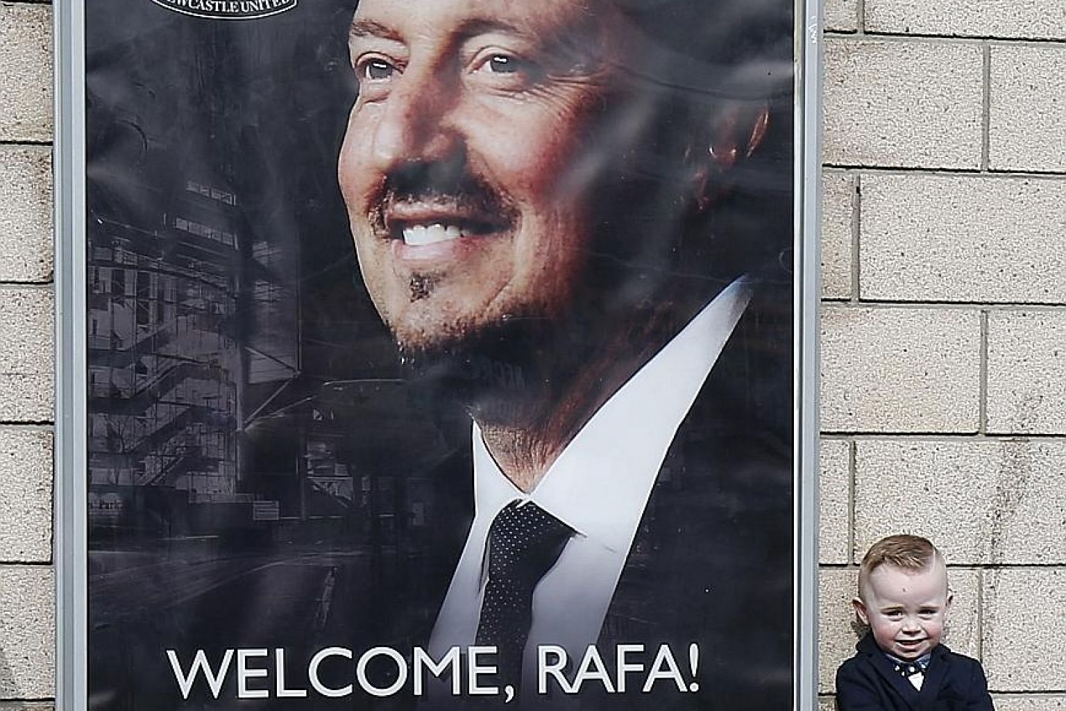 """A young fan poses next to a poster of newly appointed Newcastle United manager Rafael Benitez. The Spaniard insisted that """"we have a very good group of players and quality in the squad""""."""