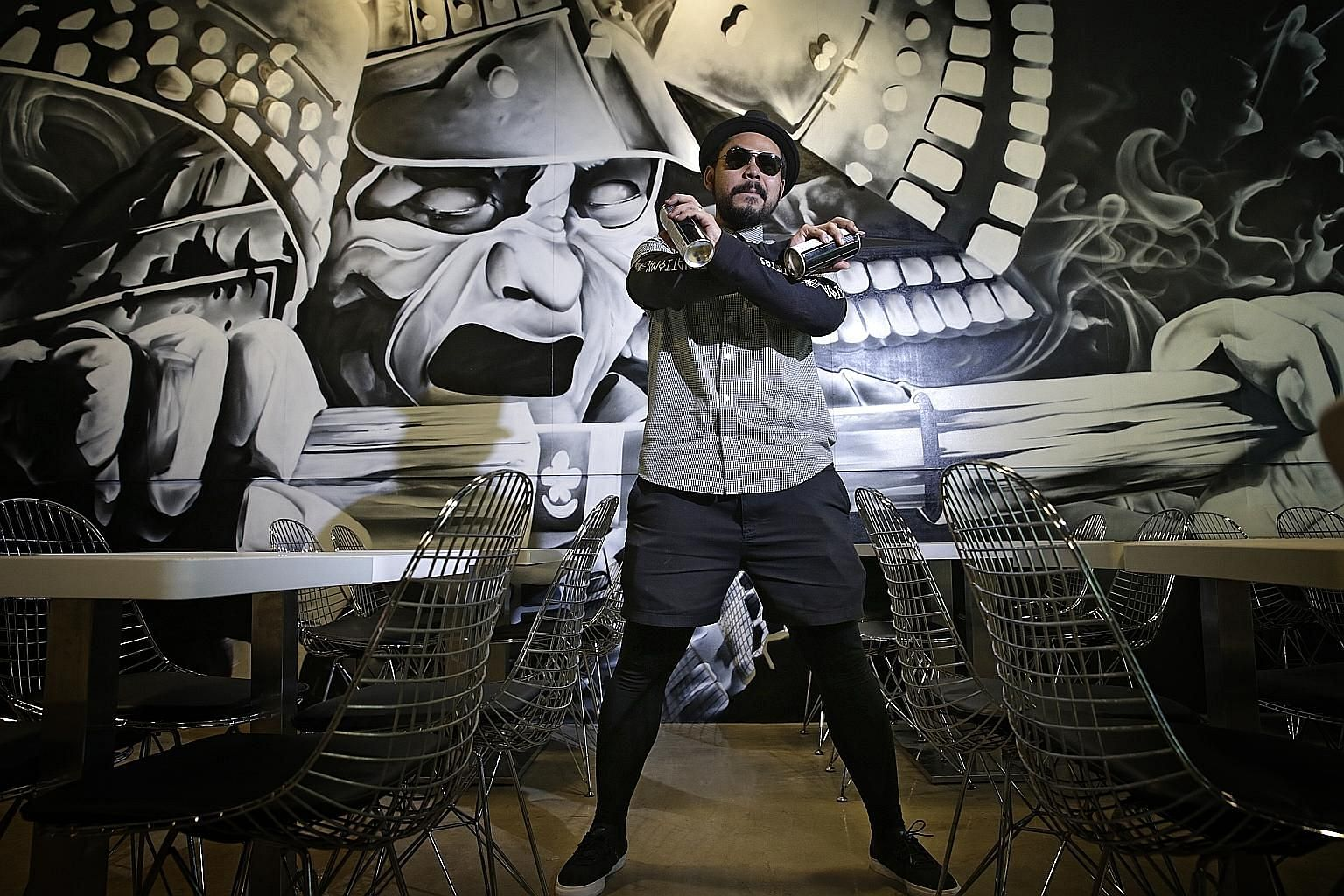 Mr Azlan, better known as Ceno2, has created several hundred graffiti artworks in Chicago and New York, and has also done numerous local pieces. He is pictured here with an artwork that he did for a local restaurant.