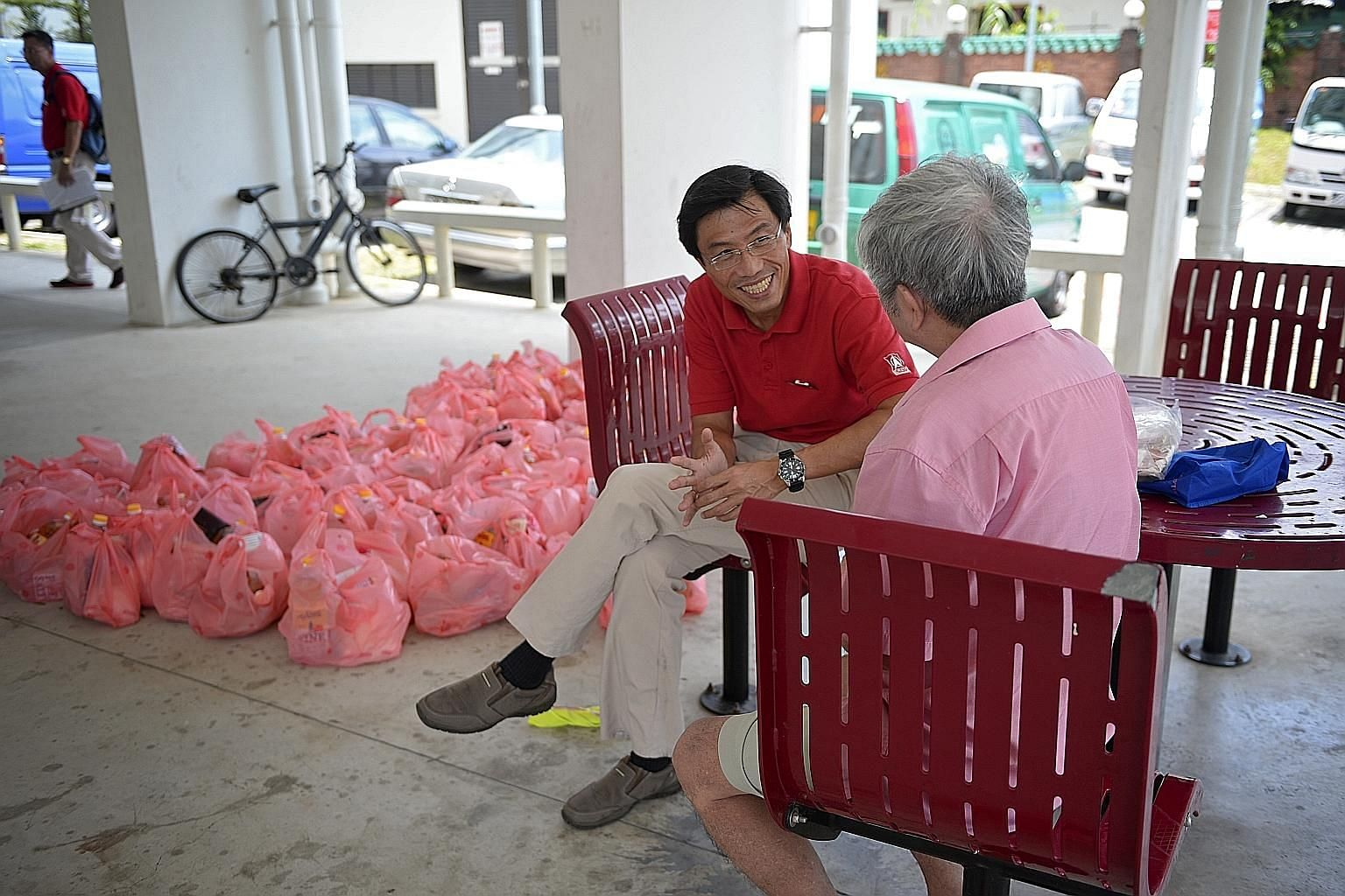 SDP's Dr Chee talking to a resident before he and his team distributed groceries in Block 210A, Bukit Batok Street 21, yesterday.