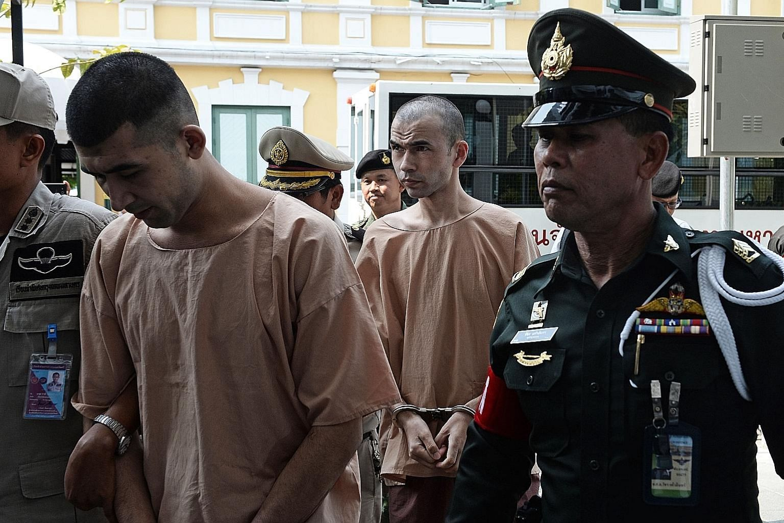 Mieraili (left) and Karadag (centre) under police escort at a military court in Bangkok yesterday. Both are Uighur Muslims. Police have issued arrest warrants for 15 other people in connection with the Aug 17 blast.