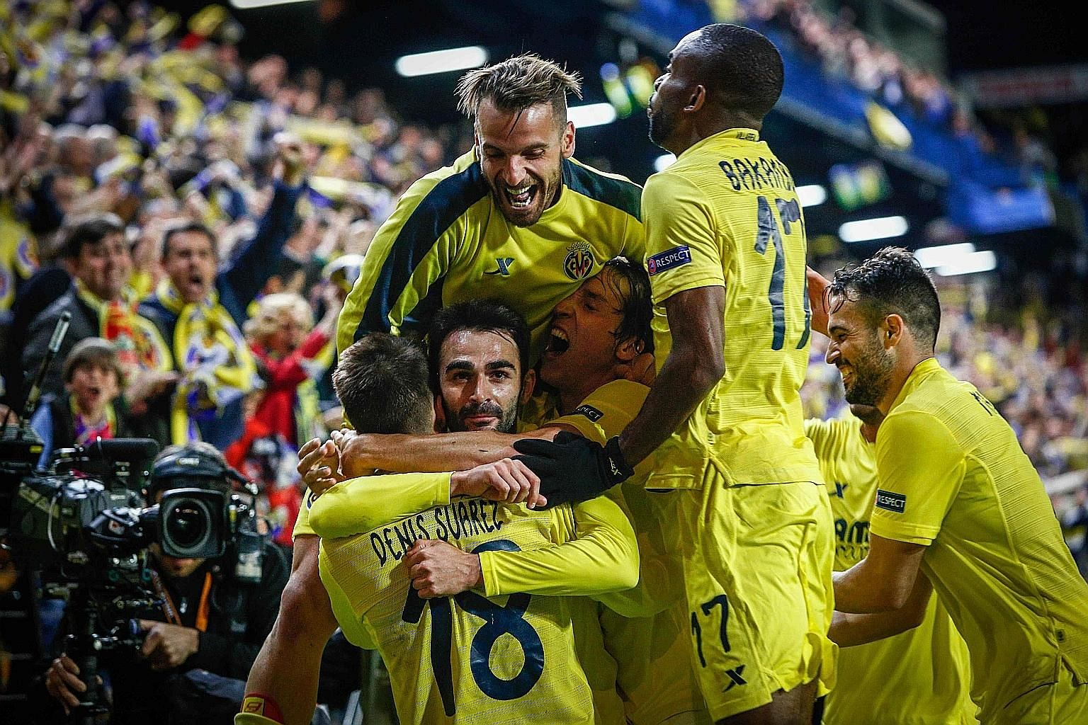 Villarreal forward Adrian Lopez (centre) celebrates his late winner against Liverpool with his team-mates on Thursday. They will go to Anfield next week with a 1-0 lead in the Europa League semi-final.