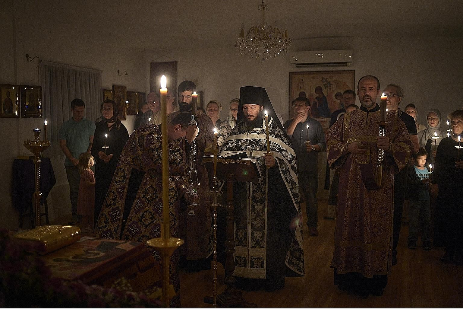Father Pitirim leading parishioners in prayer. He is dressed in black to mourn the death of Jesus Christ. An embroidered cloth that represents the burial shroud of Jesus is at the bottom left-hand corner of the picture. Father Pitirim baptising two-m