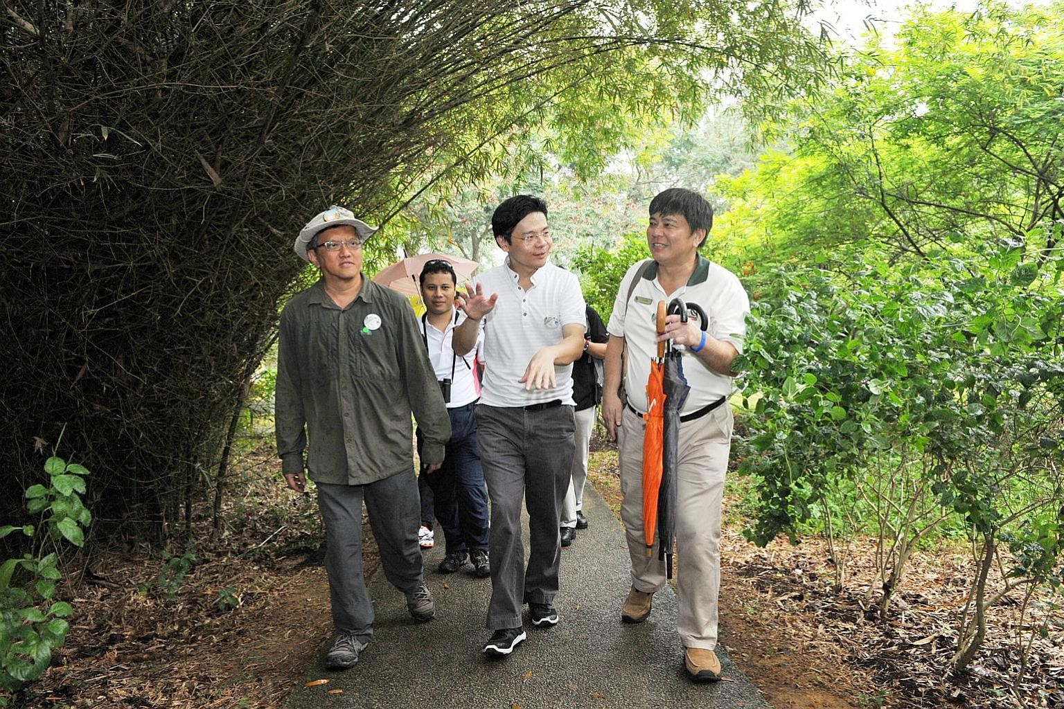 Mr Lawrence Wong (centre) with (from far left) ButterflyCircle founder Khew Sin Khoon, Senior Minister of State for National Development Desmond Lee (behind) and NParks' director for Pulau Ubin Robert Teo Chee Hin on a butterfly trail on Pulau Ubin.