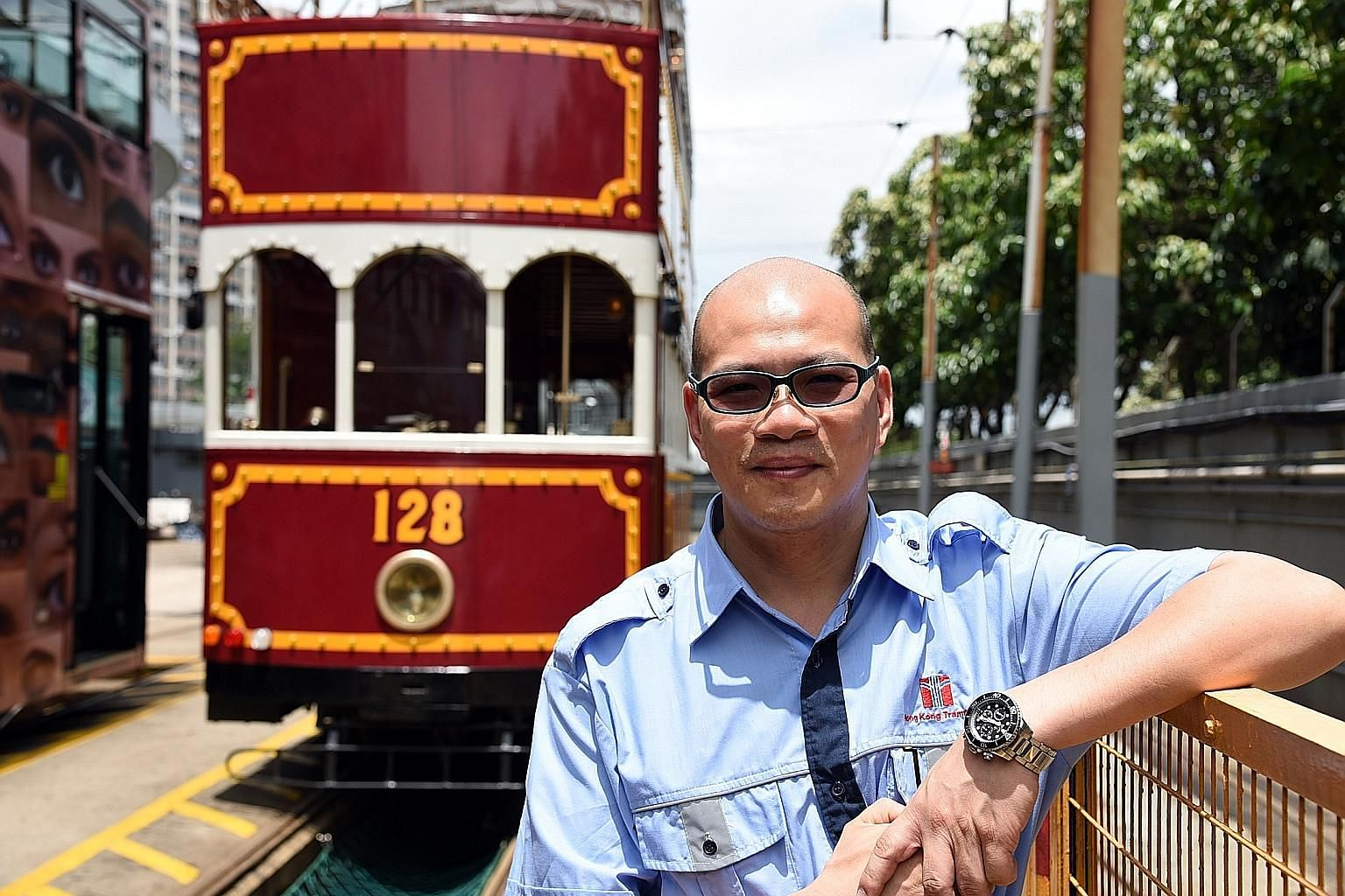 Tram captain Chan Siu Chung remembers a memorable trip when he helped a young man propose - successfully - to his girlfriend on board an antique tram (behind him).
