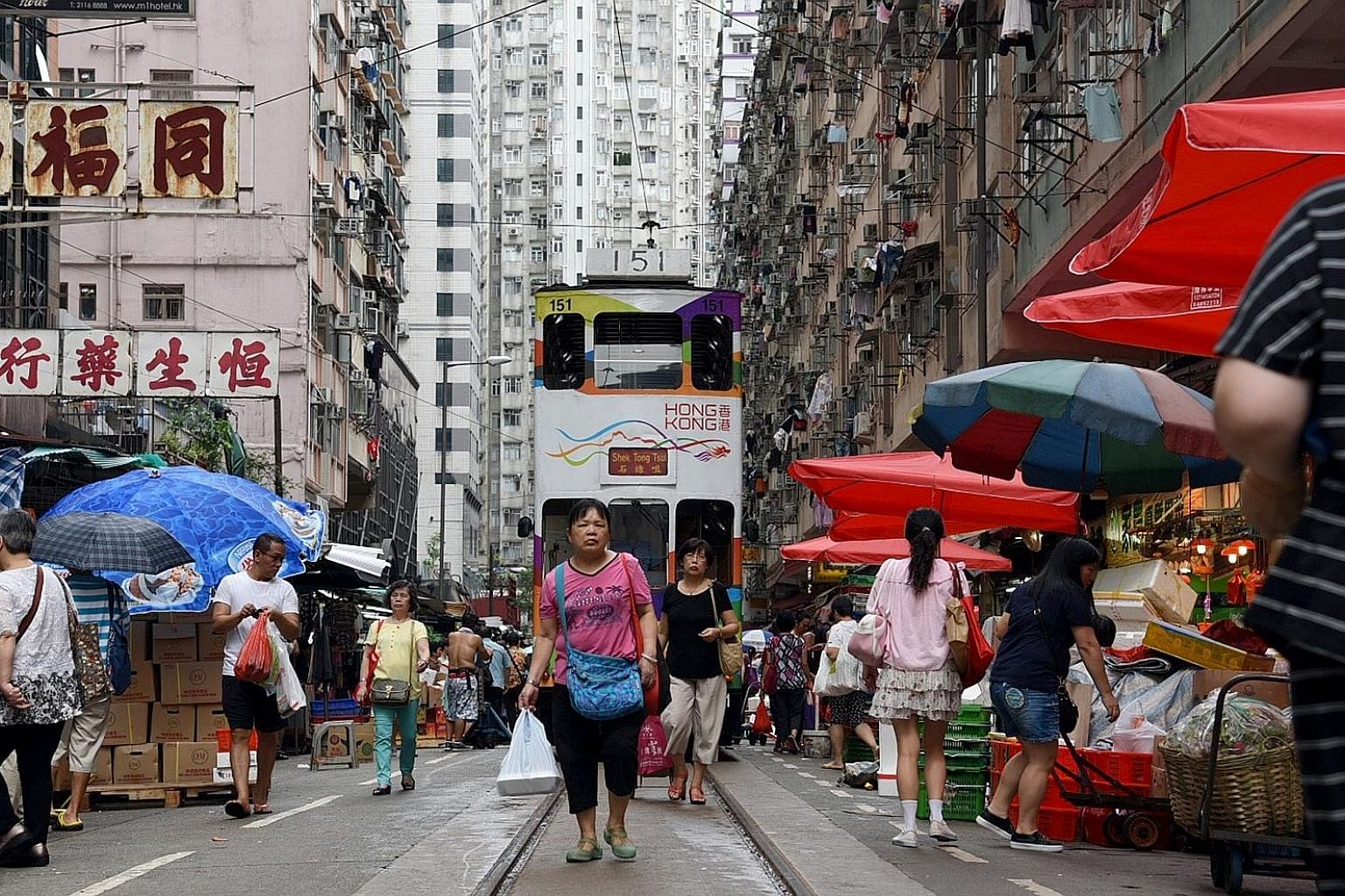 Ding ding, the tram operator will sound the bell as the tram tries to pass through the market in North Point - the only section of a tram route in Hong Kong that runs through a wet market.