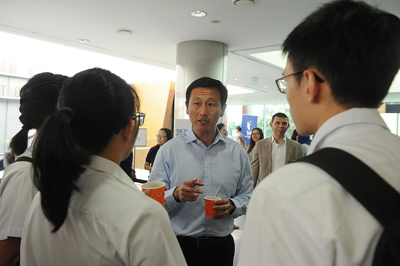 Mr Ong Ye Kung interacting with students before The Straits Times Education Forum 2016, with ST editor Warren Fernandez behind him.