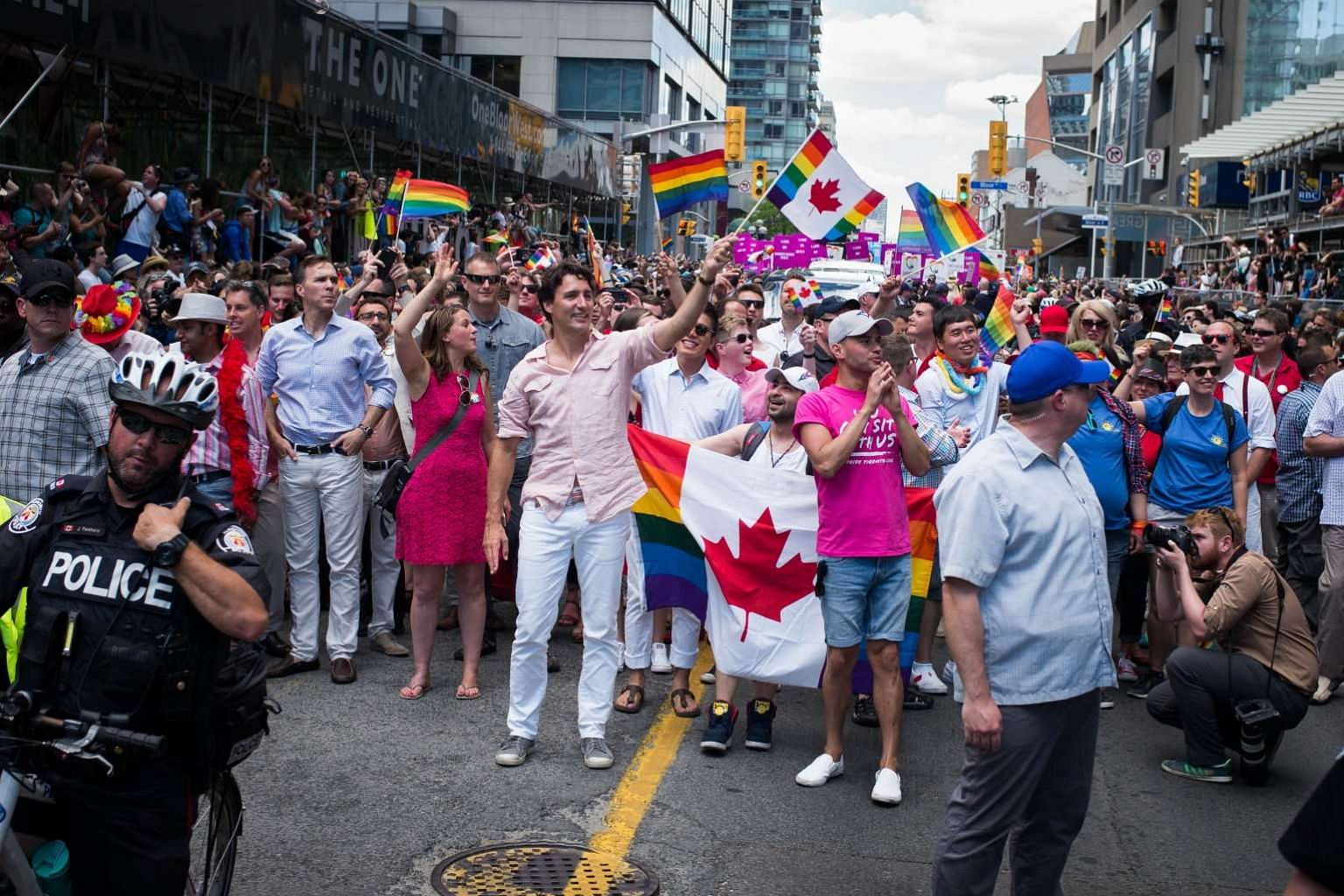 Canadian PM Justin Trudeau (middle, in pink shirt and white trousers) marching in the Pride Festival parade on July 3, 2016 in Toronto.