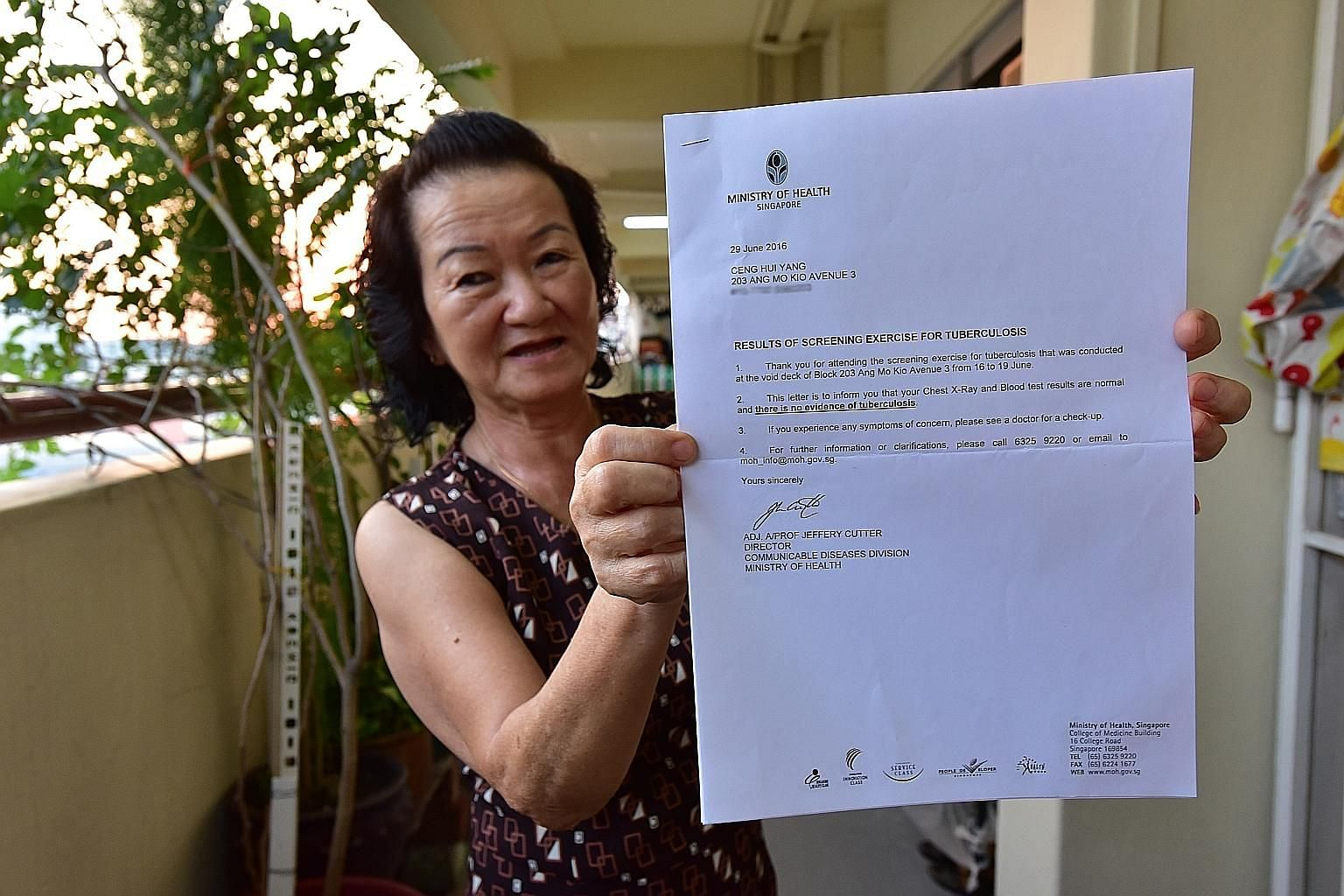 Madam Ceng, a retiree, said she has faith that the Government will contain any spread of tuberculosis. She is seen here showing her letter of clearance after she went for TB screening.
