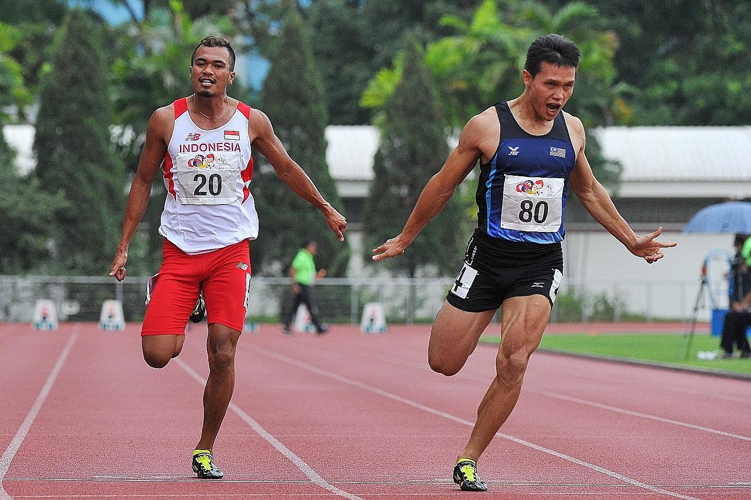 Jonathan Nyepa (right) of Malaysia winning gold in the Asean University Games 100m in 10.62sec at Choa Chu Kang Stadium yesterday. Indonesia's Iswandi Iswandi (No. 20) won the bronze behind Vietnam's Le Trong Hinh.