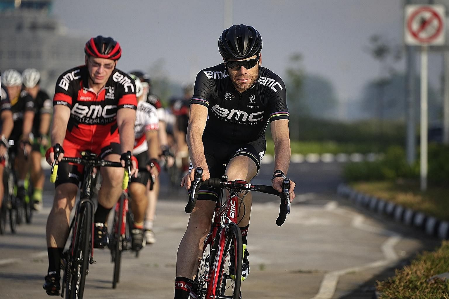 Former Tour de France winner Cadel Evans (in black), a global ambassador for the BMC racing team, followed by cyclists from the Singapore Cycling Federation at Seletar yesterday.