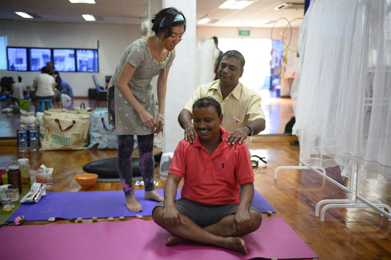 "Welders Krishna Rai (in yellow), 50, and Athi Ramamoorthy, 32, learning the art of massage at a ""roadside spa"", guided by artist Ng Xi Jie, during the Kapor ChatParty held at Kampong Kapor on Sunday."