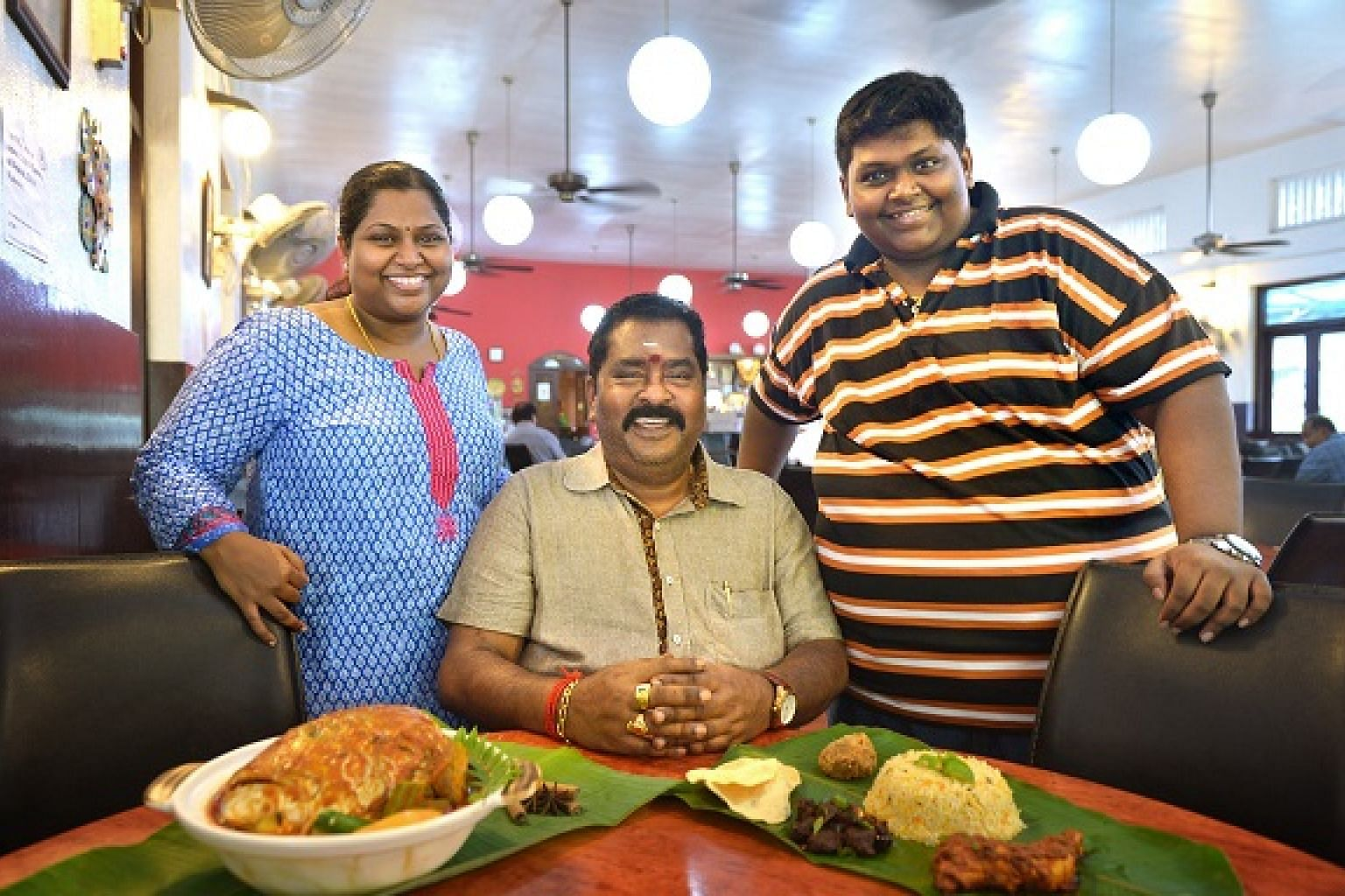 Mr V Maheyndran (centre) with his daughter Nagajyothi Mahendran and son M Veerasamy, who both run Samy's Curry.