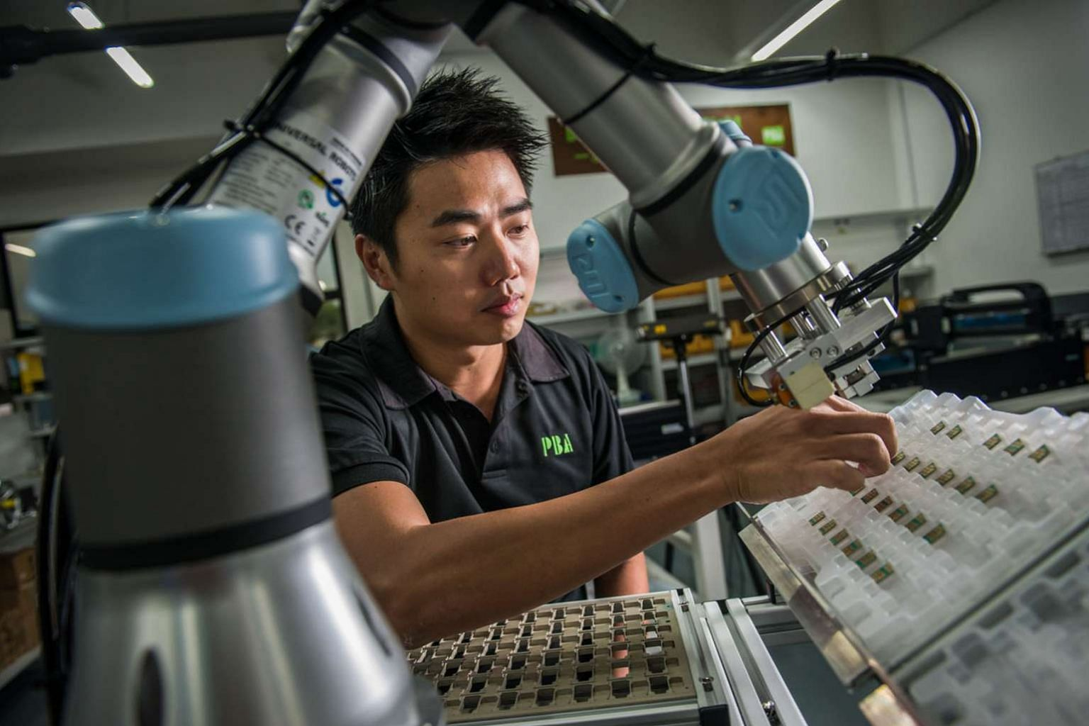 "Mr Yap arranging chips on a collaborative robot pick- and-place robotic cell. His company is now moving into robotics as factories become more ""humanless""."