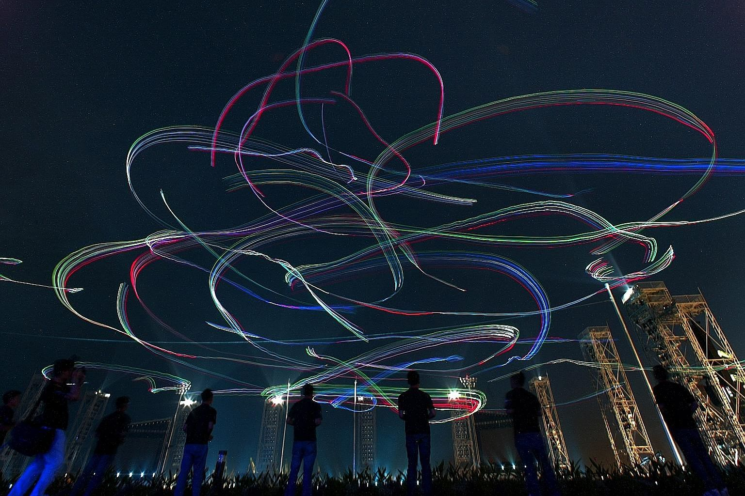 The night sky was transformed into a kaleidoscope of colours as radio-controlled illuminated kites – piloted by 42 people from toy kite maker GoFlyKite and the Army – whizzed around in the wind, captured in a long exposure shot during the 2007 NDP preview