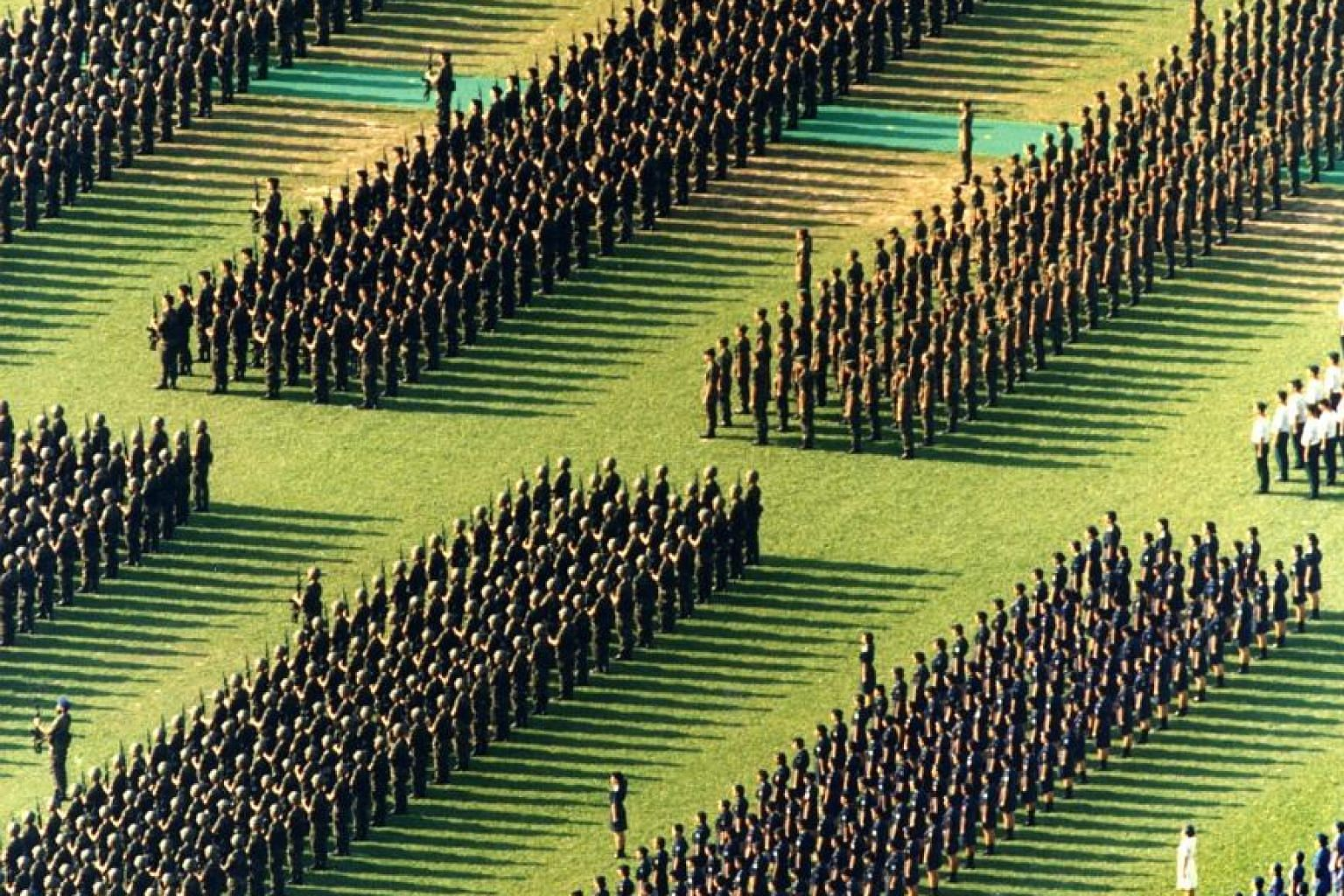 Marching contingents standing ramrod-straight for a rifle salute at the NDP rehearsal at the Padang in 1993.