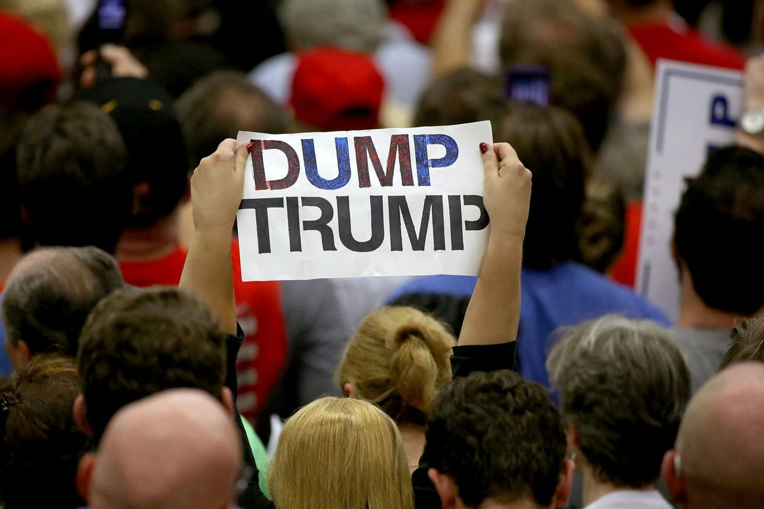 A protester with an anti-Trump sign at a campaign event for Mr Trump in Fairfield, Connecticut in the US. Every poll released since the Republican and Democratic parties held their conventions in July shows a growing gap between Mr Trump and Democratic Pa