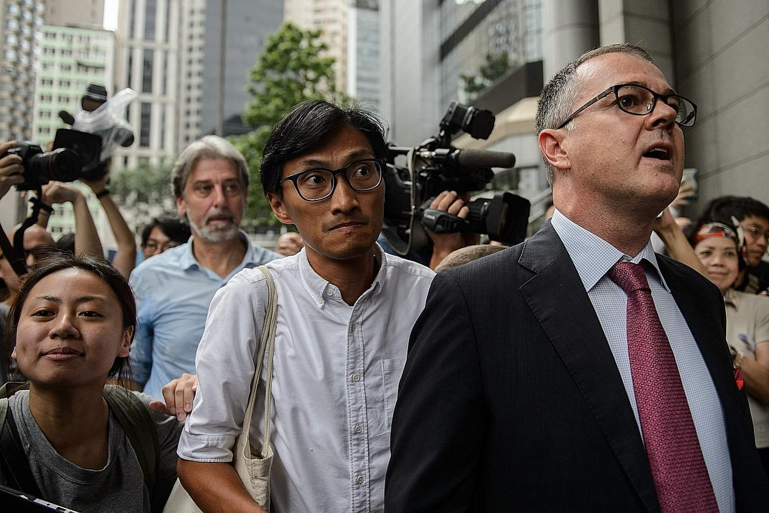"""Social activist-turned-lawmaker Eddie Chu (centre) and lawyer Michael Vidler arriving at Wan Chai Police headquarters yesterday. Mr Chu said he had received """"credible death threats"""" against him and his family."""