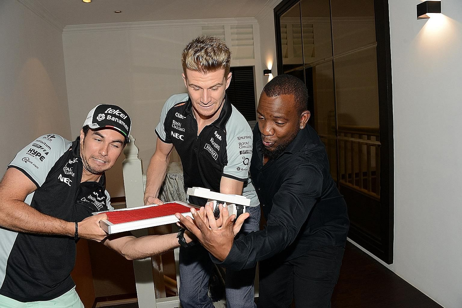 Force India drivers Sergio Perez (left) and Nico Hulkenberg (centre) fumbling with the Felio Siby watches in front of Dominique Siby, the founder of Felio Siby and a sponsor of the Force India team.