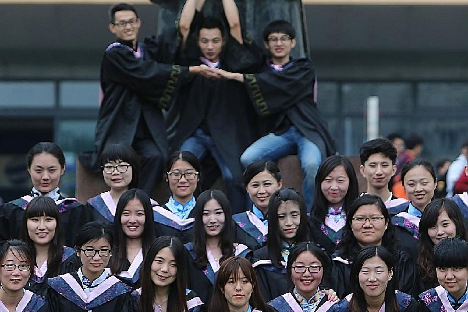 College graduates posing beside a statue of ancient Chinese philosopher Confucius at Qingdao University in eastern China. The broadening of access to university in China is undermining the quality of education.