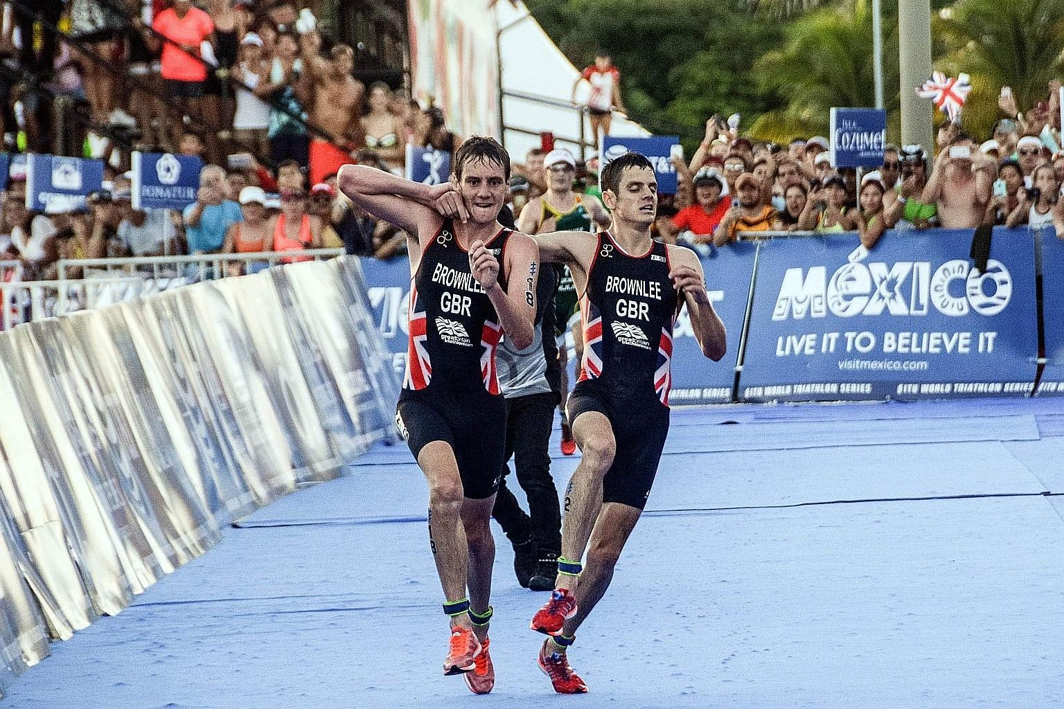 "British athlete Alistair Brownlee (left) helping his younger brother Jonathan across the line during the World Triathlon Championships in Mexico on Sept 18. ""It was a natural human reaction,"" the older sibling said after the race."