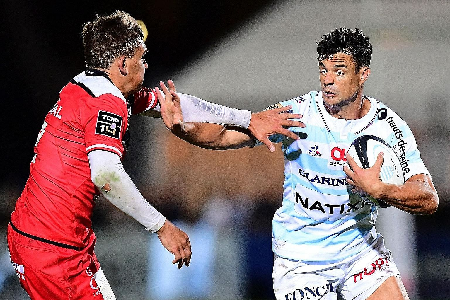 Racing's Kiwi fly-half Dan Carter trying to get past Toulouse's English fly-half Toby Flood in their match last month. He and two team-mates failed a drug test after the previous Top 14 season's final but the two Kiwis are said to have been allowed t