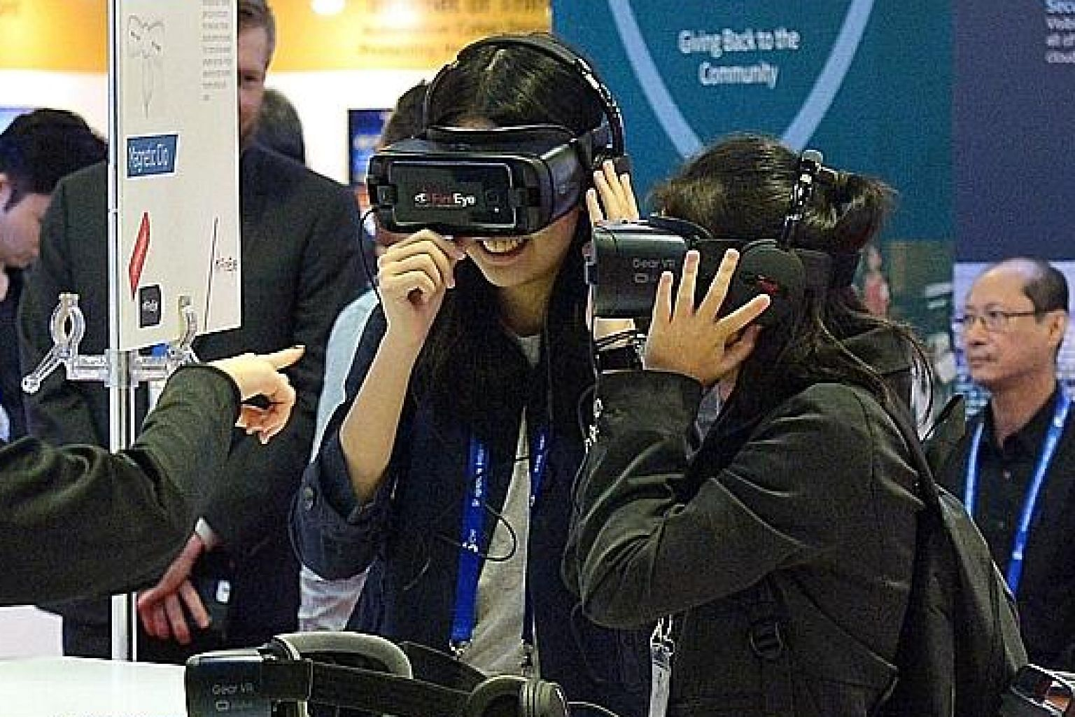 Visitors trying out virtual reality goggles at a booth at the inaugural Singapore International Cyber Week at Suntec Convention and Exhibition Centre yesterday.