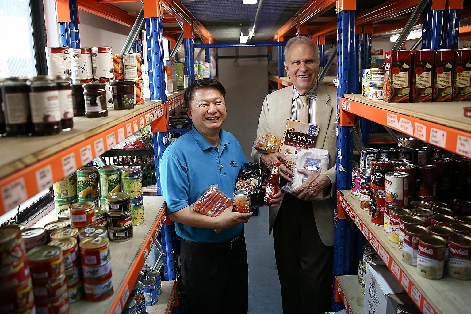 Food from the Heart executive director Anson Quek (left) and chairman Ronald Stride redistribute near-expiry items and goods with damaged packaging.